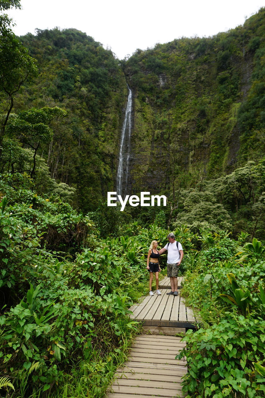 Couple standing in forest against waterfall