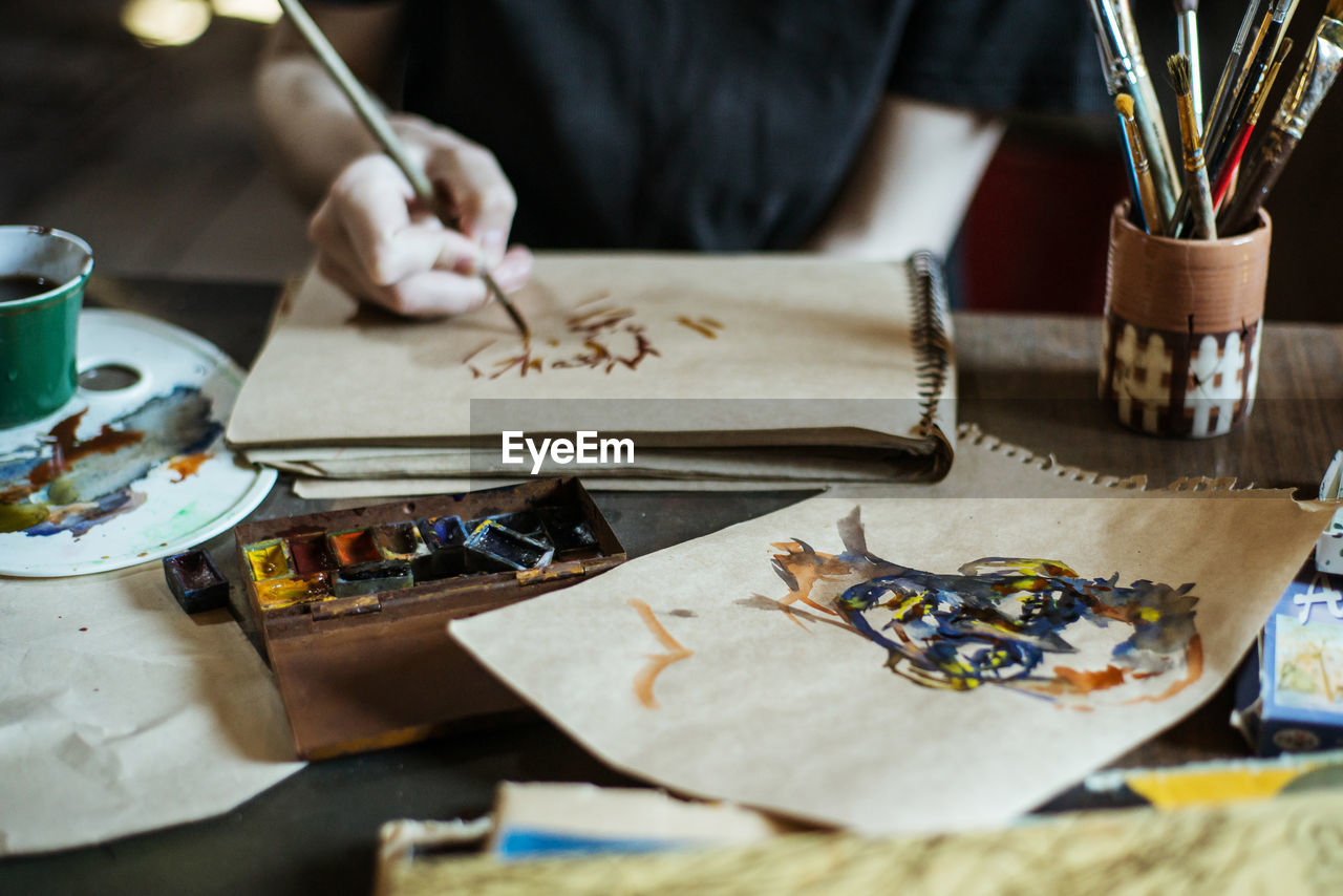 table, art and craft, one person, indoors, creativity, real people, paper, craft, selective focus, skill, publication, holding, book, paintbrush, occupation, brush, high angle view, human hand, close-up, hand, art and craft equipment