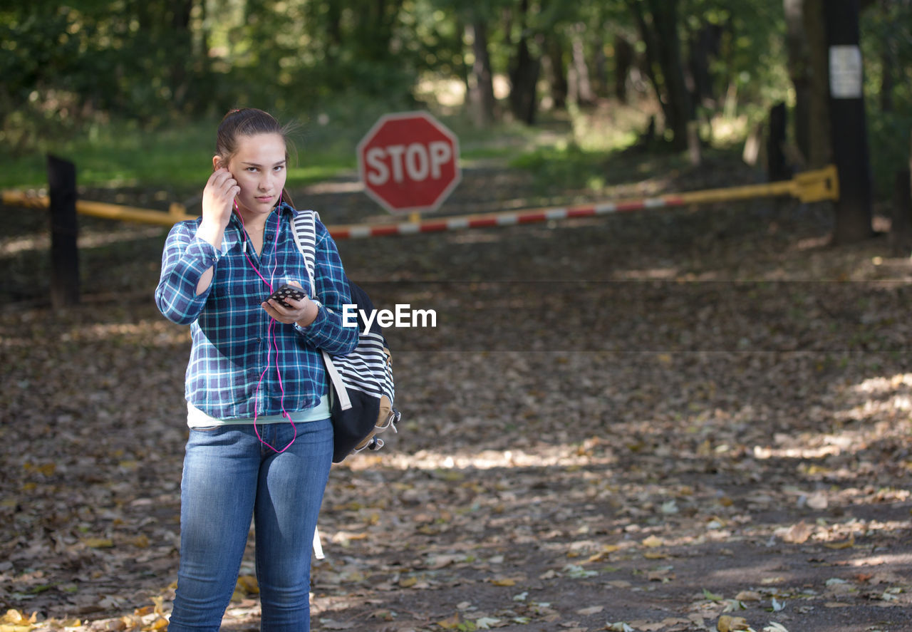 Portrait of teenage girl listening music over mobile phone while standing on land