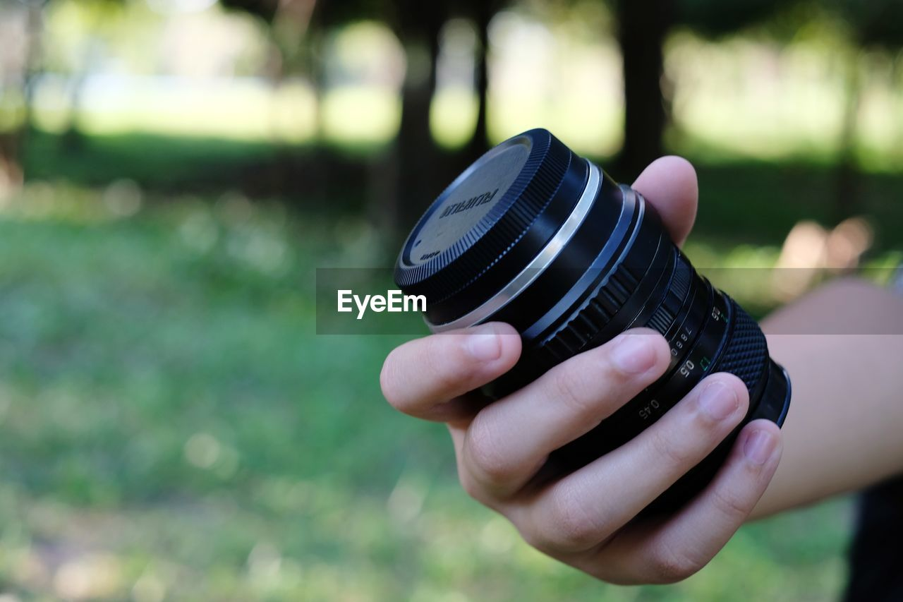 human hand, hand, focus on foreground, human body part, holding, real people, day, one person, photography themes, technology, camera - photographic equipment, leisure activity, lifestyles, digital camera, close-up, nature, body part, photographic equipment, human finger, finger, outdoors, slr camera