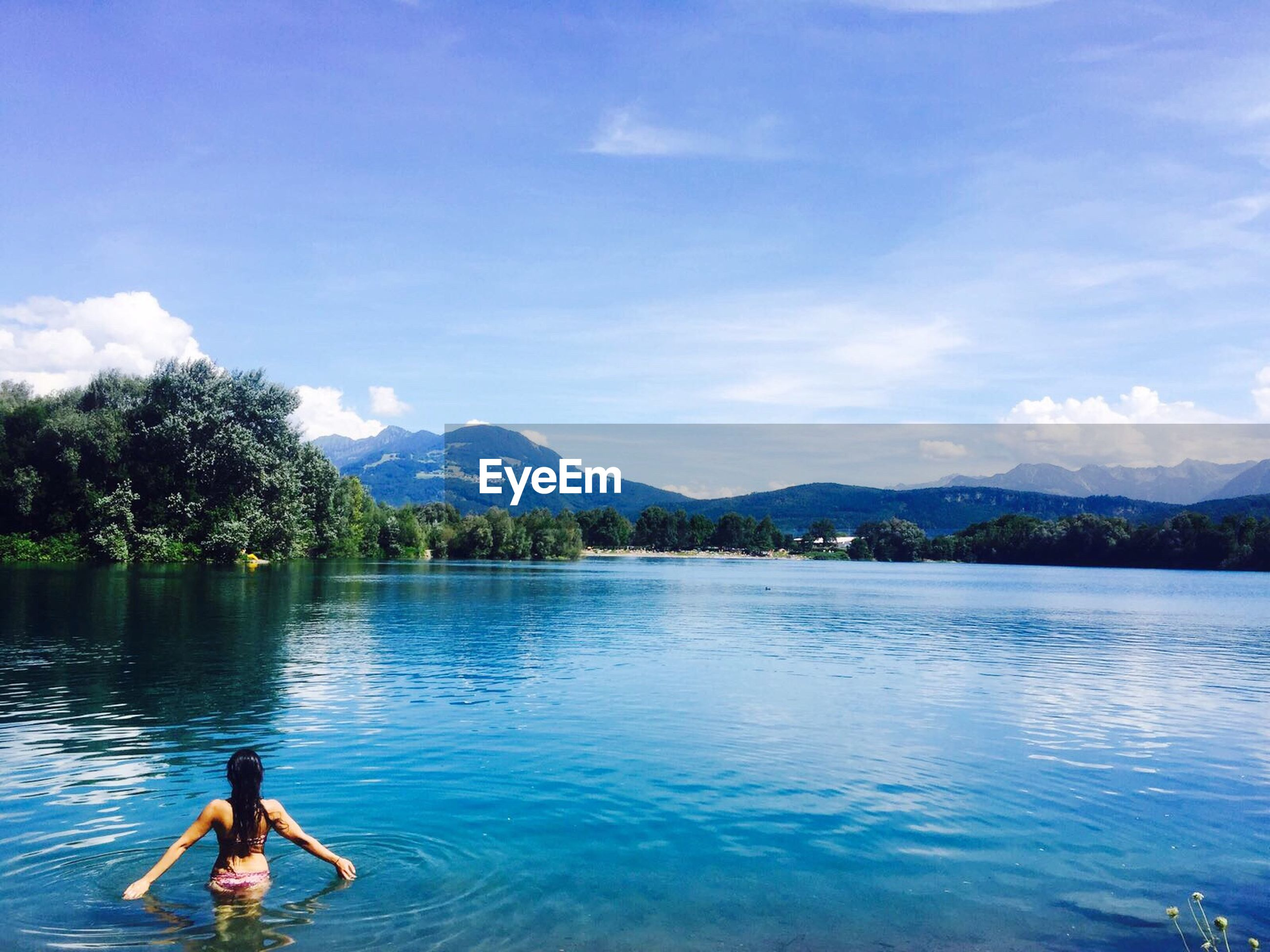 water, mountain, sky, one person, lake, leisure activity, tree, day, cloud - sky, nature, outdoors, waterfront, beauty in nature, real people, scenics, swimming, young adult, people