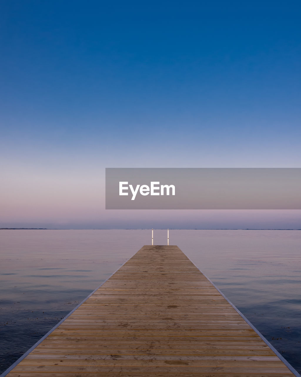 sky, pier, water, wood - material, scenics - nature, jetty, beauty in nature, tranquil scene, sea, tranquility, direction, no people, copy space, horizon over water, nature, clear sky, the way forward, sunset, blue, diminishing perspective, outdoors, wood paneling, long