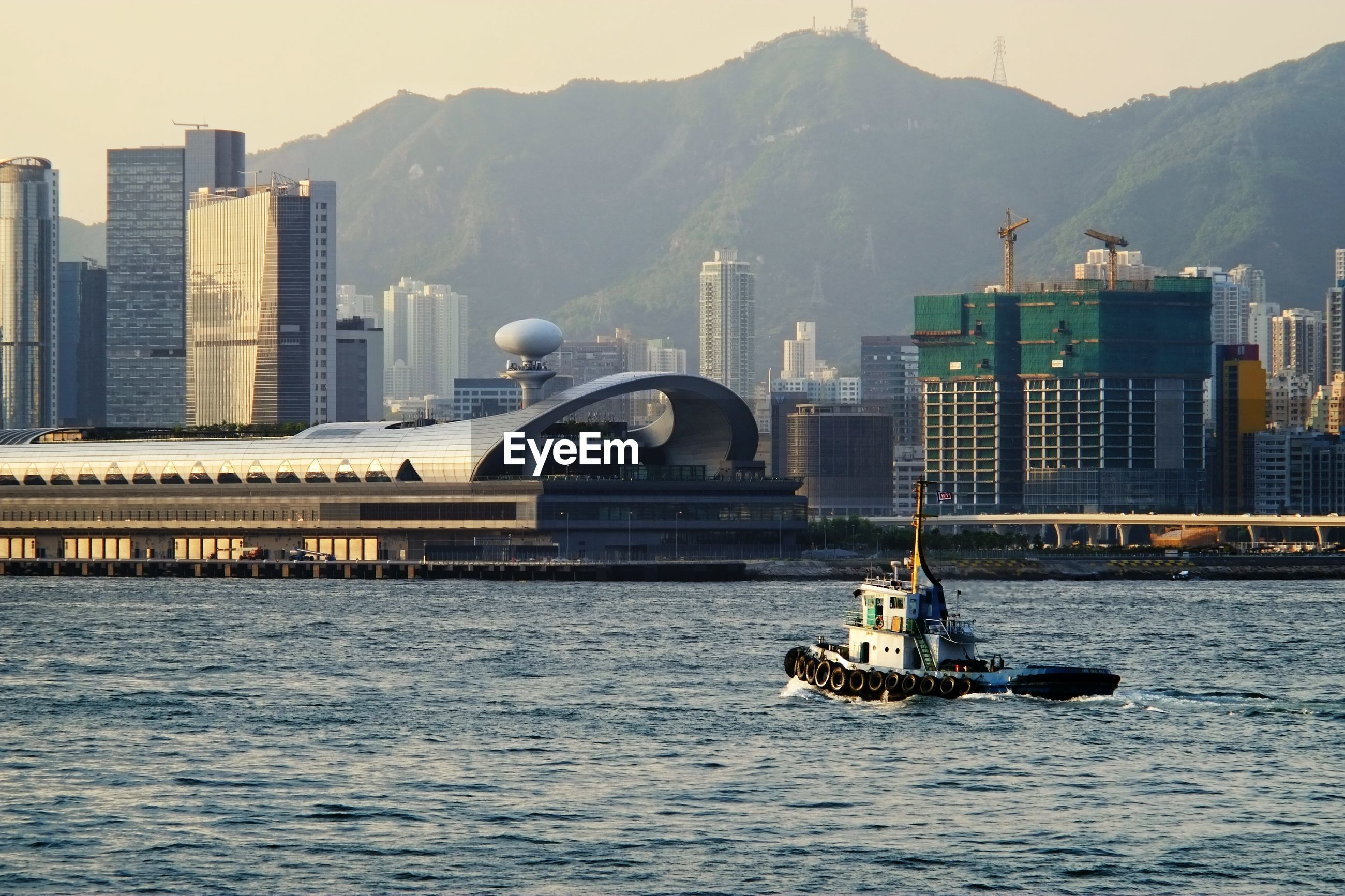 Nautical vessel sailing on river against city