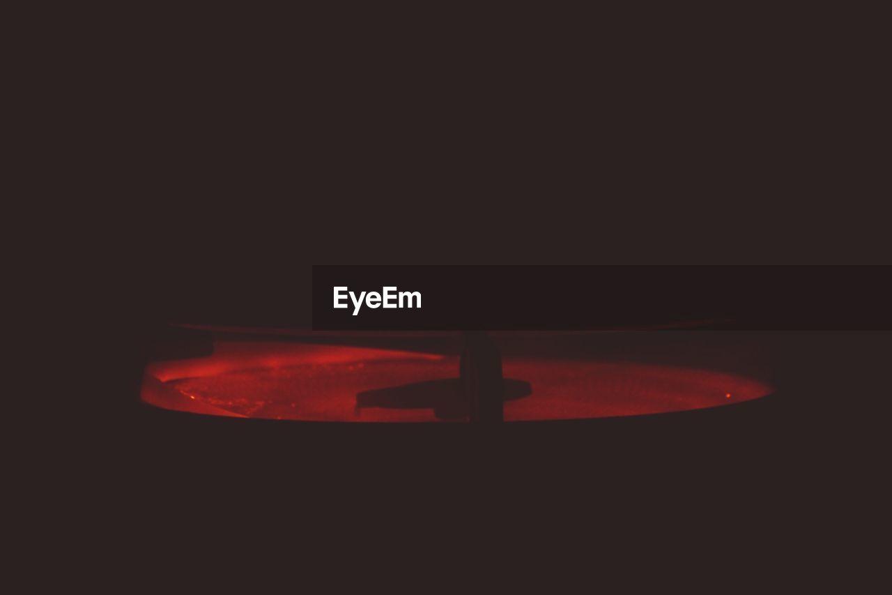 red, no people, indoors, black background, studio shot, close-up, night