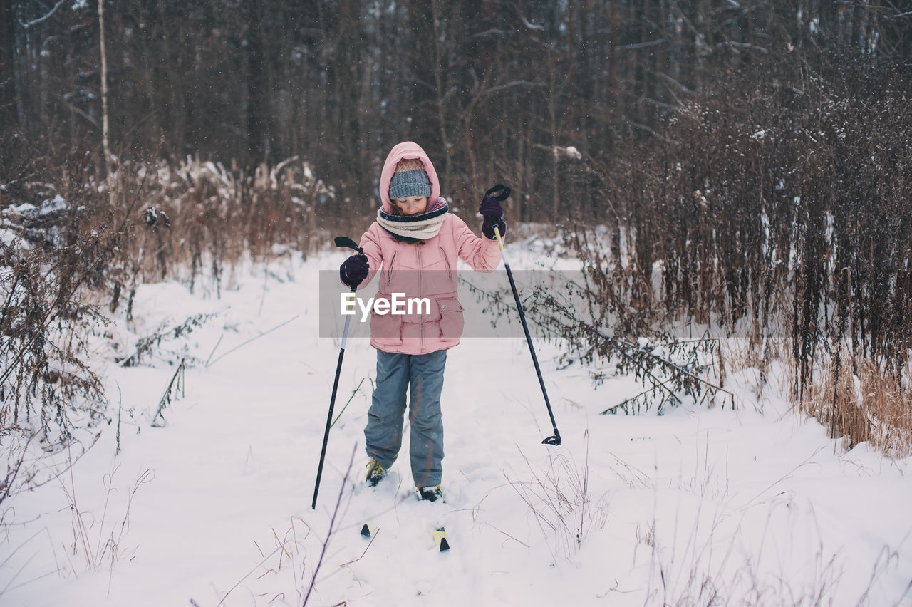 Girl Skiing On Snow Covered Field Against Bare Trees