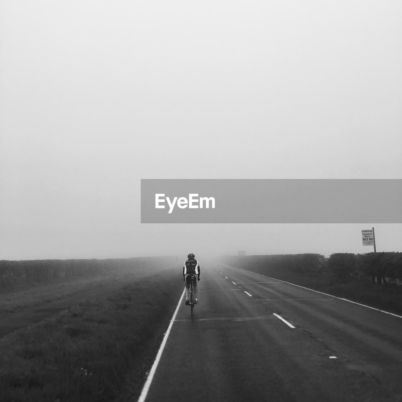 Rear View Of Man Bicycling On Country Road
