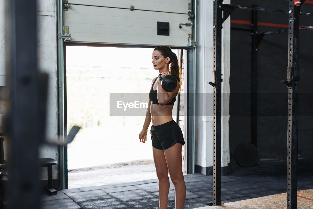 Side View Of Young Woman Lifting Kettlebell While Exercising In Gym