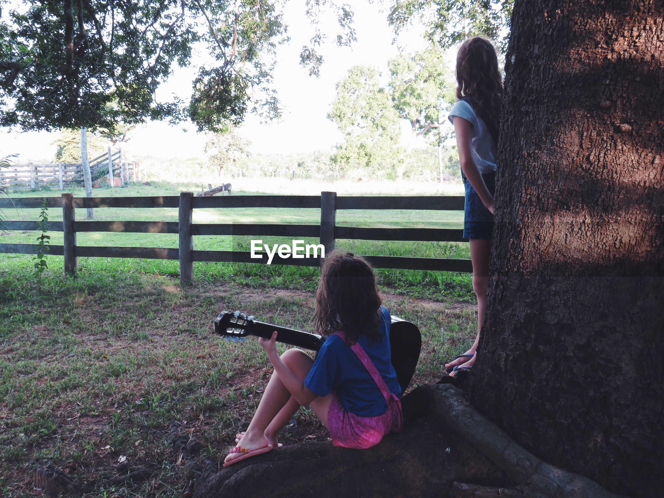 REAR VIEW OF GIRL LOOKING AT CAMERA WHILE SITTING ON TREE