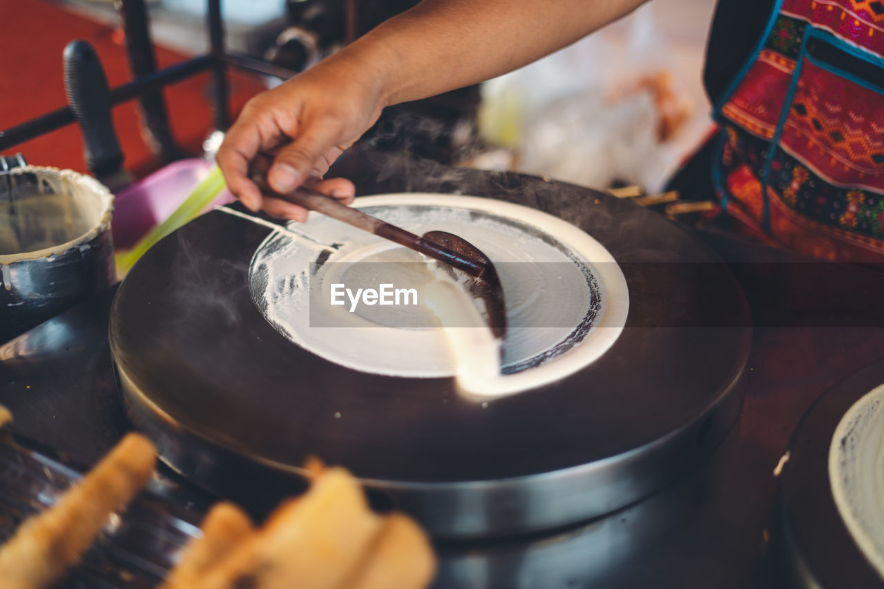 Midsection of person preparing food at market stall