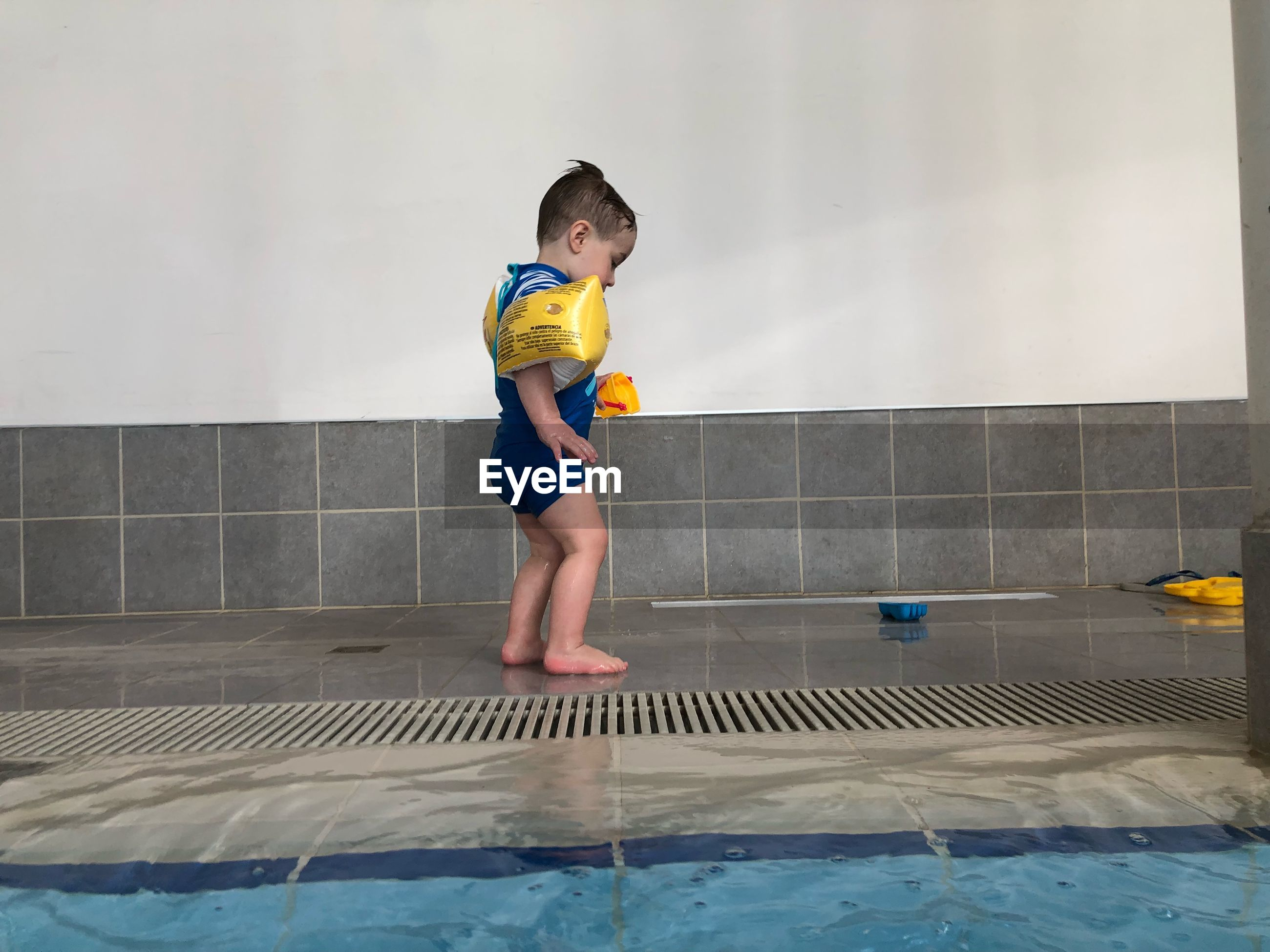 Side view of boy standing on poolside