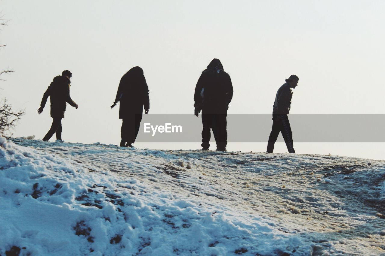 LOW ANGLE VIEW OF PEOPLE ON SNOW AGAINST SKY