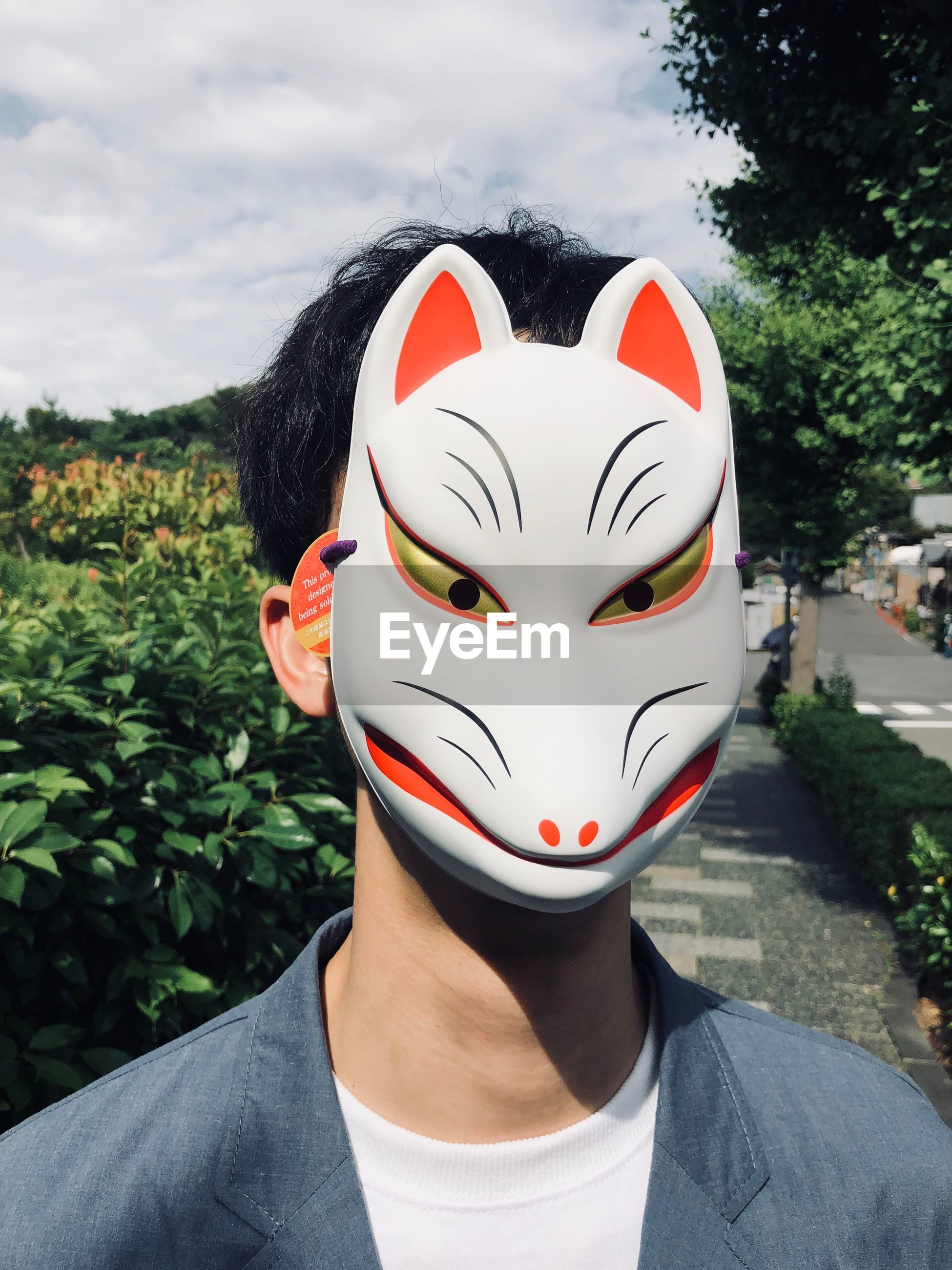 Close-up of man wearing animal mask during sunny day