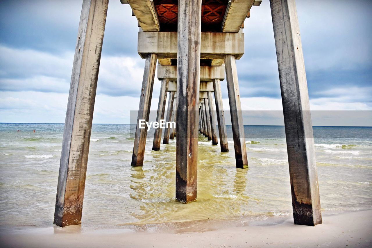 water, sea, horizon, beach, land, sky, horizon over water, cloud - sky, beauty in nature, no people, wood - material, scenics - nature, day, nature, tranquil scene, wave, sand, architecture, tranquility, outdoors, architectural column, wooden post, underneath