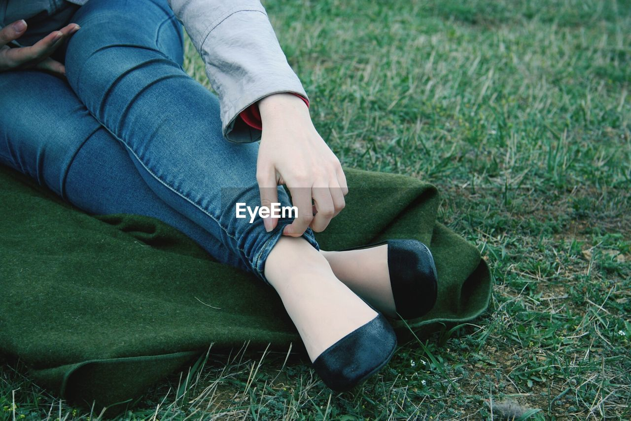 Low section of woman touching her jeans while sitting at park