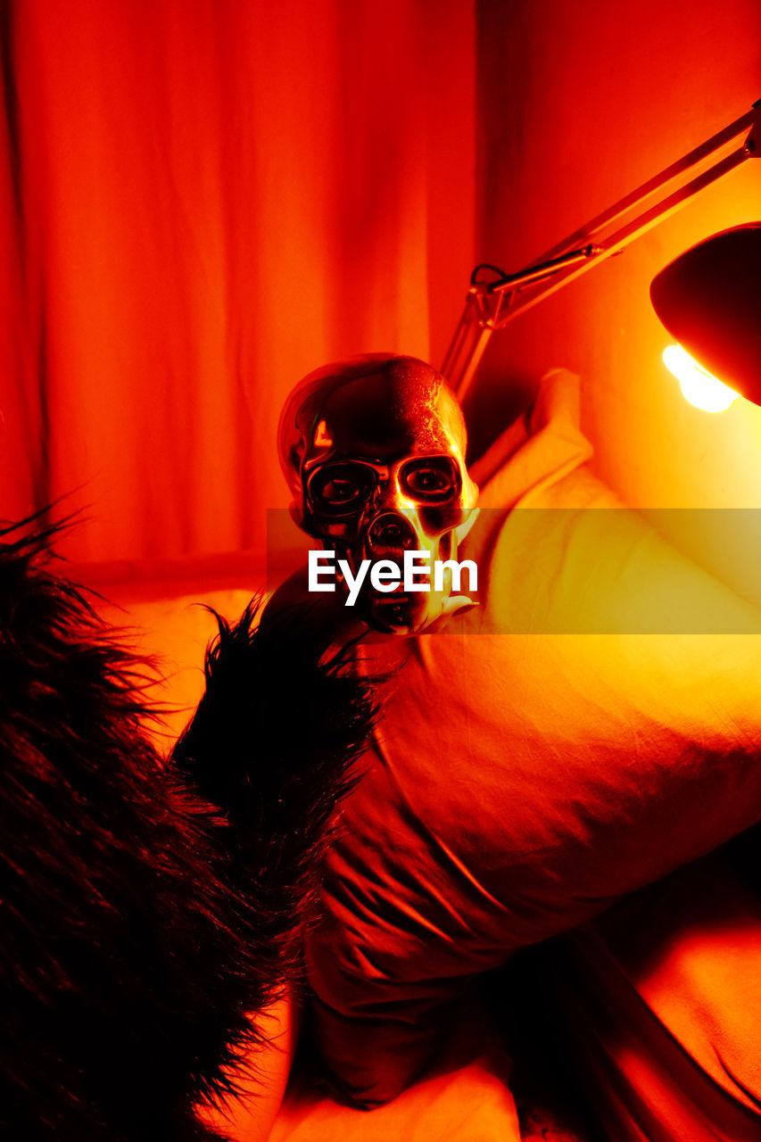 indoors, human skeleton, close-up, human body part, human skull, illuminated, people, bone, spooky, human representation, skeleton, human bone, mask, red, orange color, real people, lighting equipment, representation, body part
