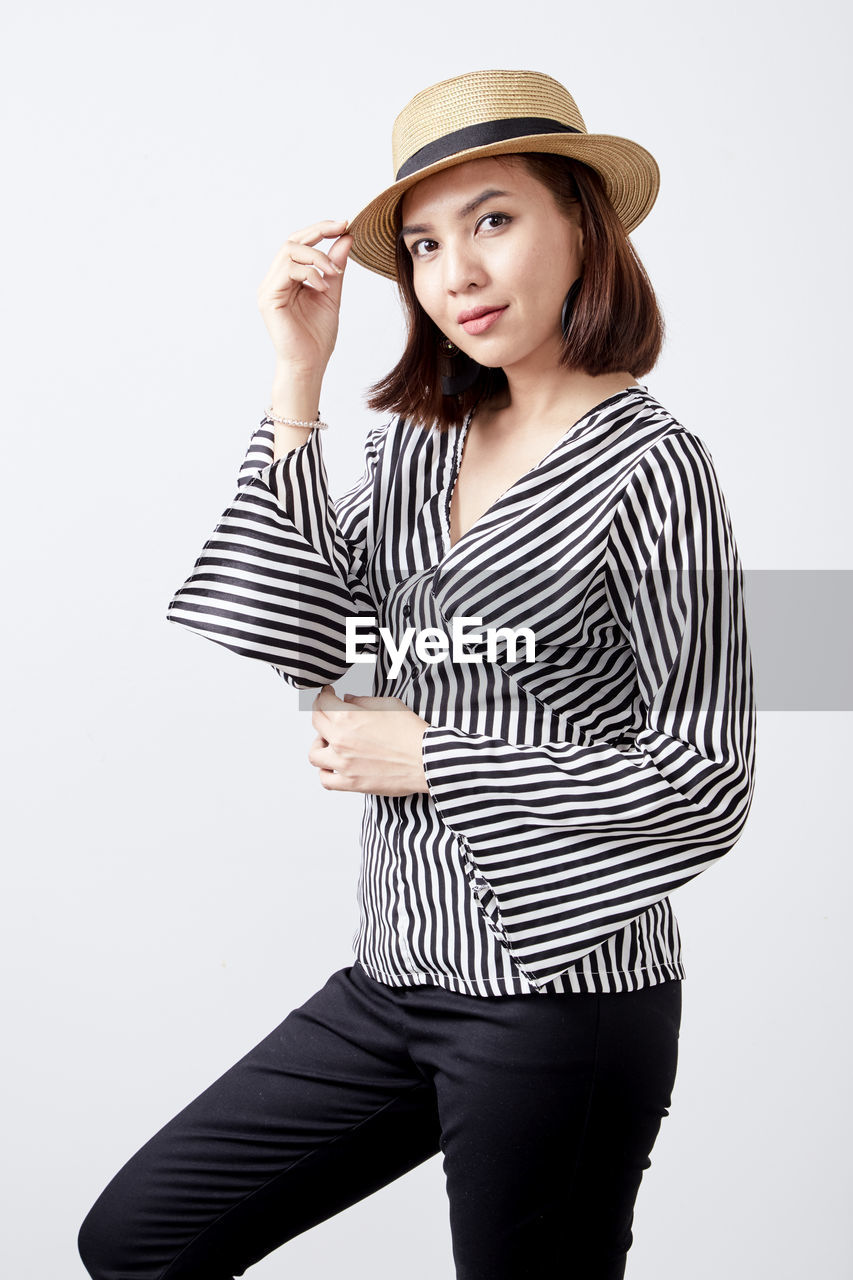 studio shot, striped, one person, white background, three quarter length, young women, young adult, clothing, indoors, casual clothing, cut out, portrait, hat, women, standing, leisure activity, beauty, looking at camera, front view, adult, beautiful woman, hairstyle, teenager