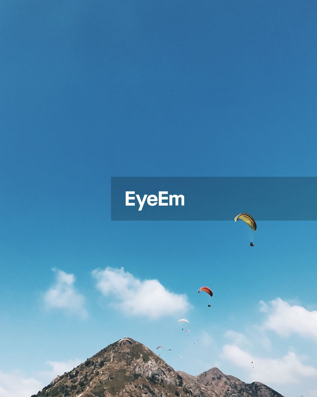 Low Angle View Of Paragliders Against Blue Sky