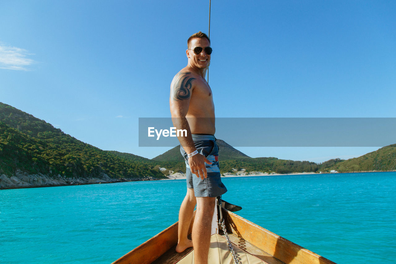 Portrait of man standing in boat on sea against sky