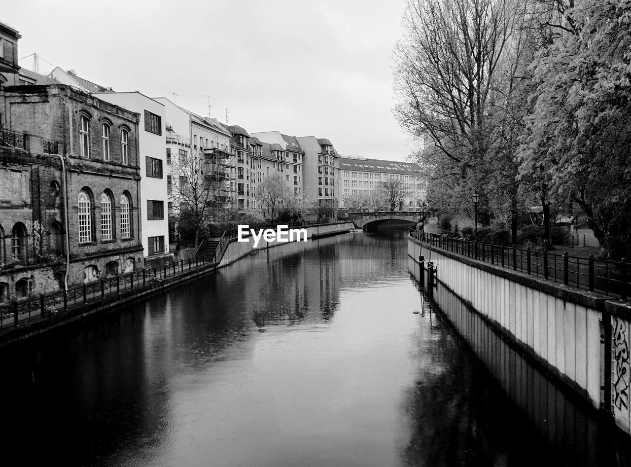 Buildings Along Canal Against Sky