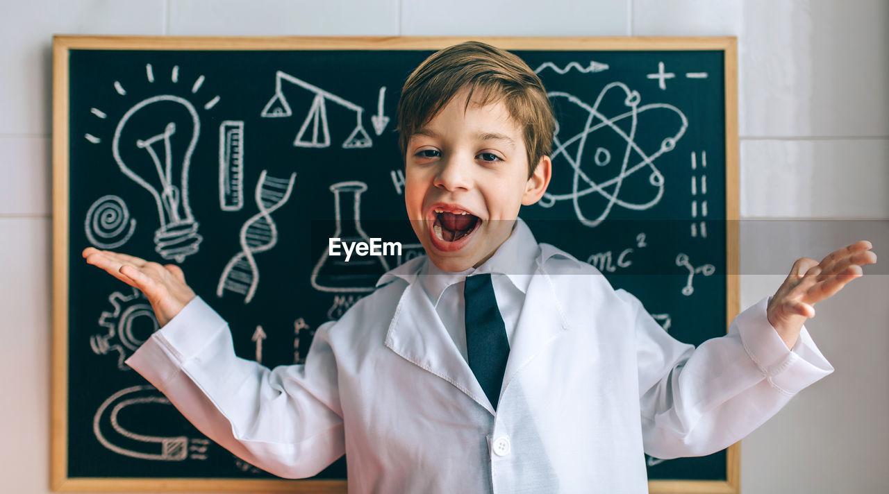 Portrait of cute boy standing against blackboard in classroom