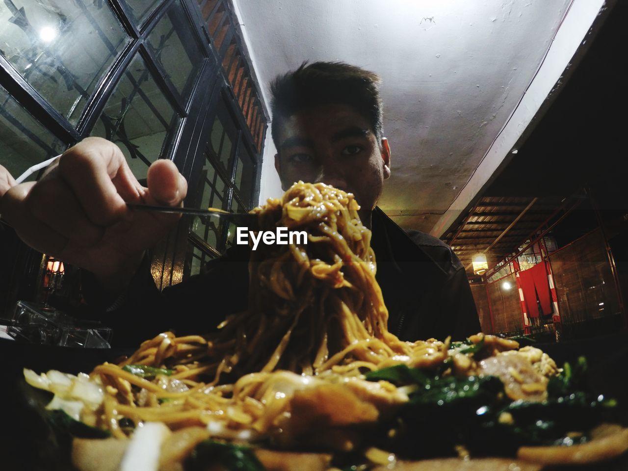 Portrait of man having noodles at restaurant