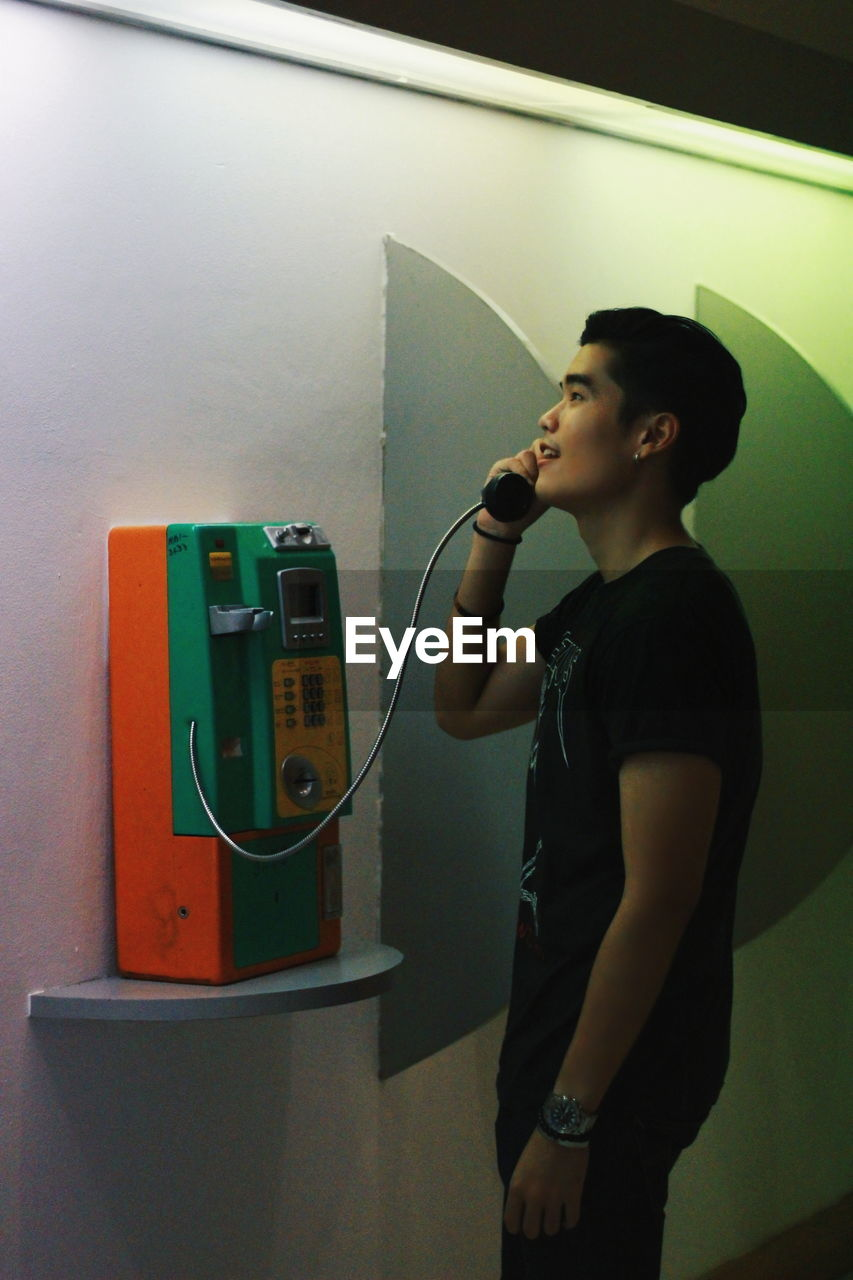 Young man using pay phone