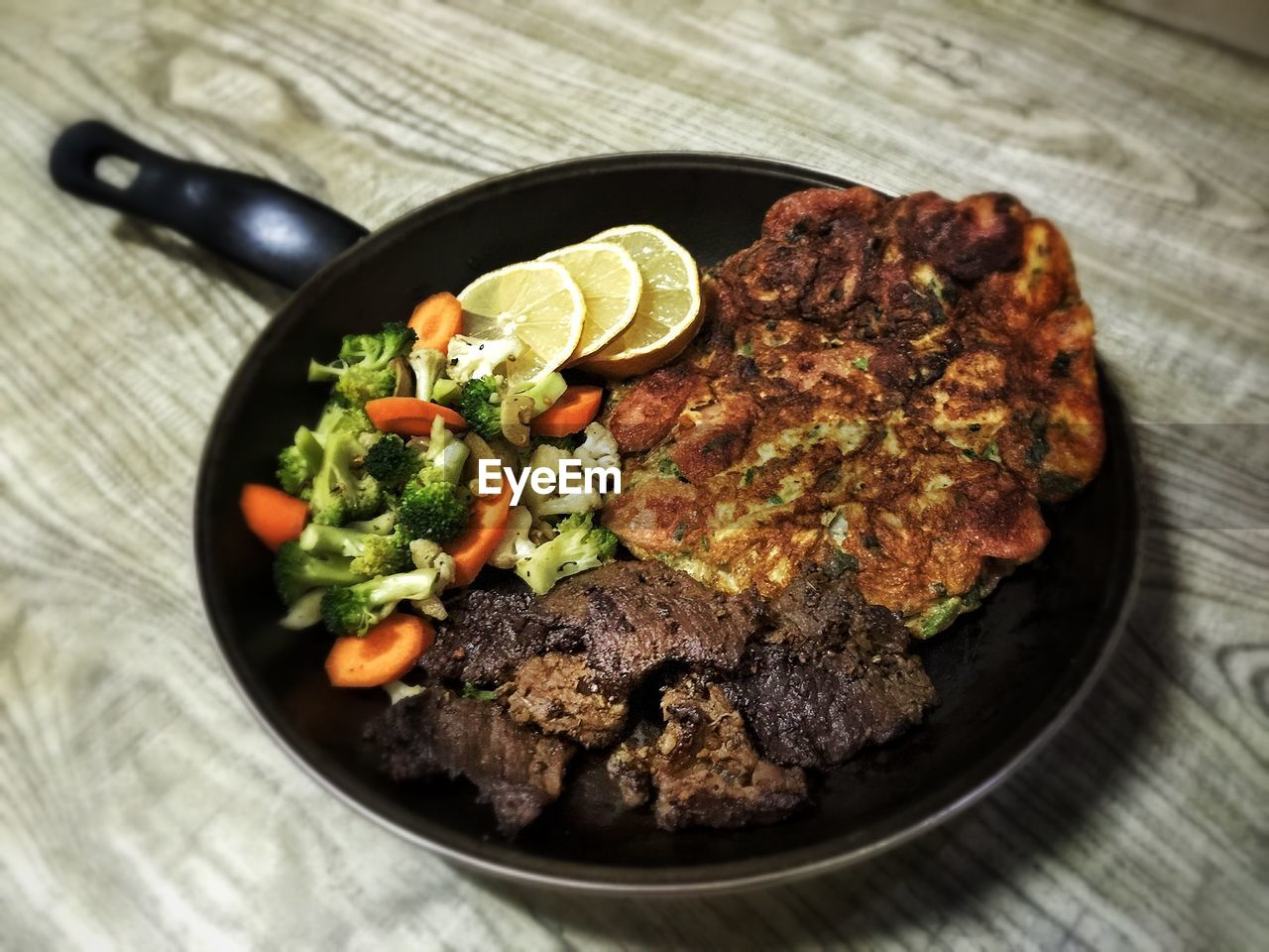 High angle view of food served in frying pan on wooden table