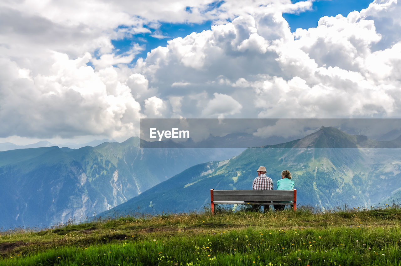 mountain, cloud - sky, beauty in nature, sky, scenics - nature, sitting, real people, mountain range, leisure activity, tranquil scene, lifestyles, seat, plant, nature, day, grass, non-urban scene, men, environment, bench, outdoors