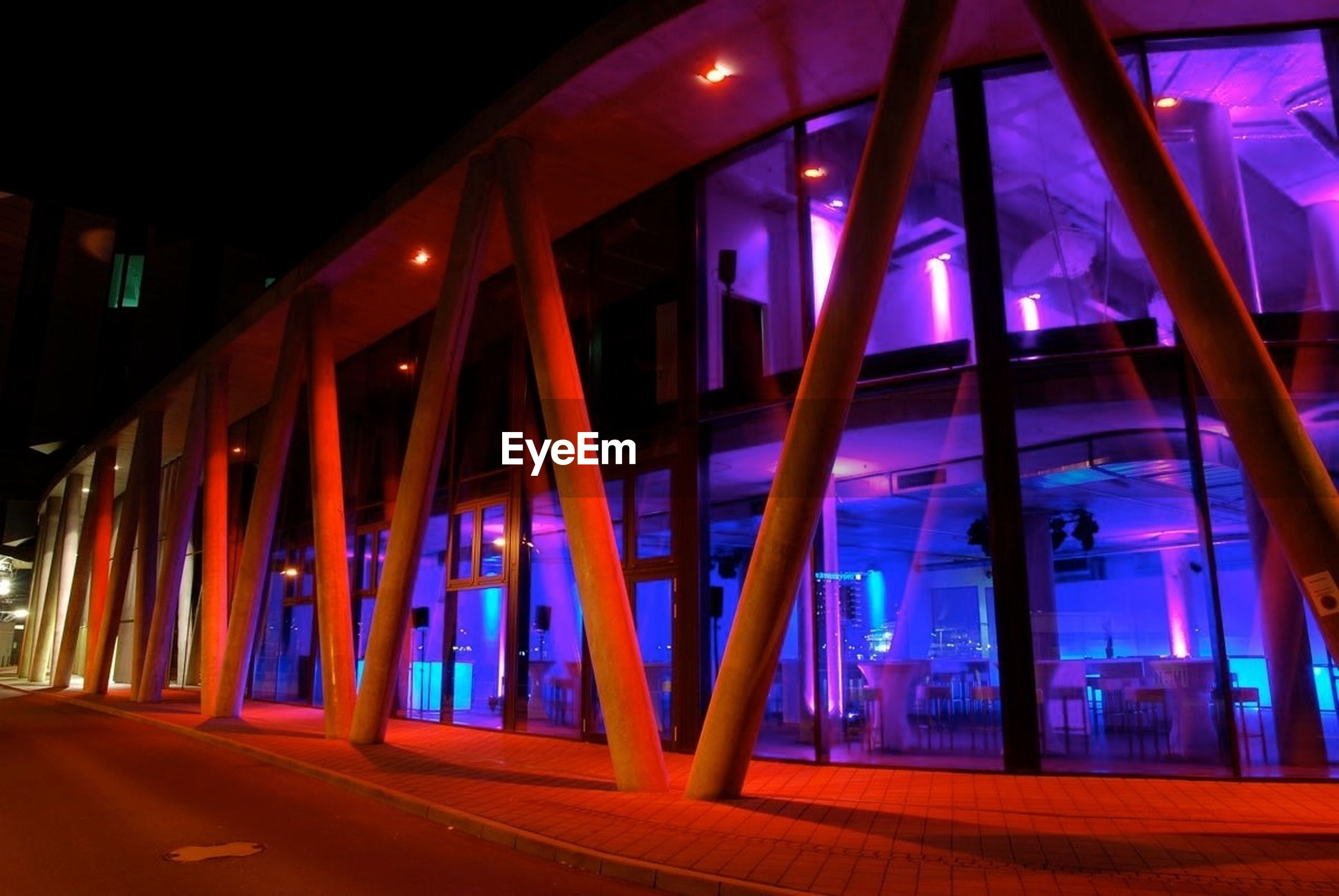 Illuminated walkway by buildings during night