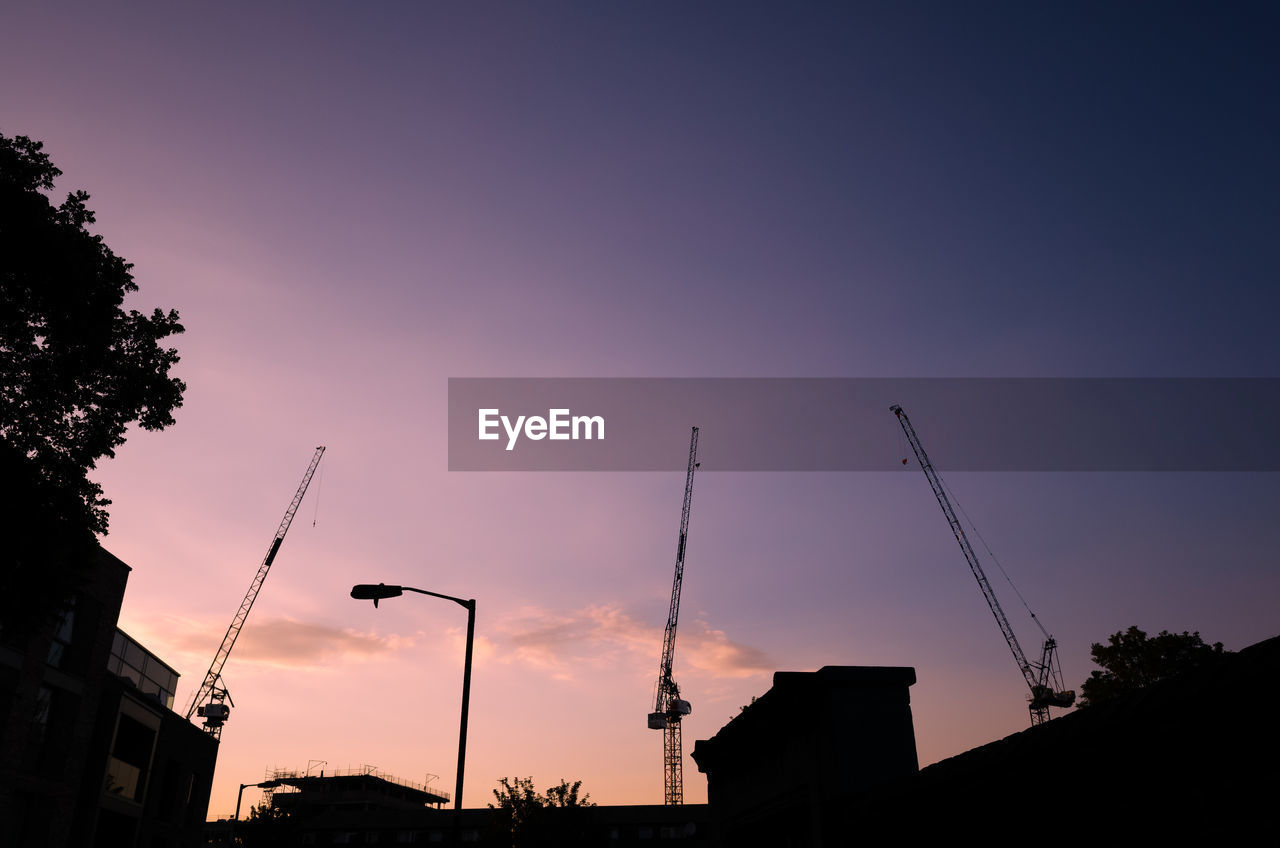 sky, building exterior, sunset, built structure, architecture, silhouette, crane - construction machinery, industry, nature, no people, construction industry, low angle view, machinery, orange color, cloud - sky, factory, construction site, outdoors, building, development, construction equipment