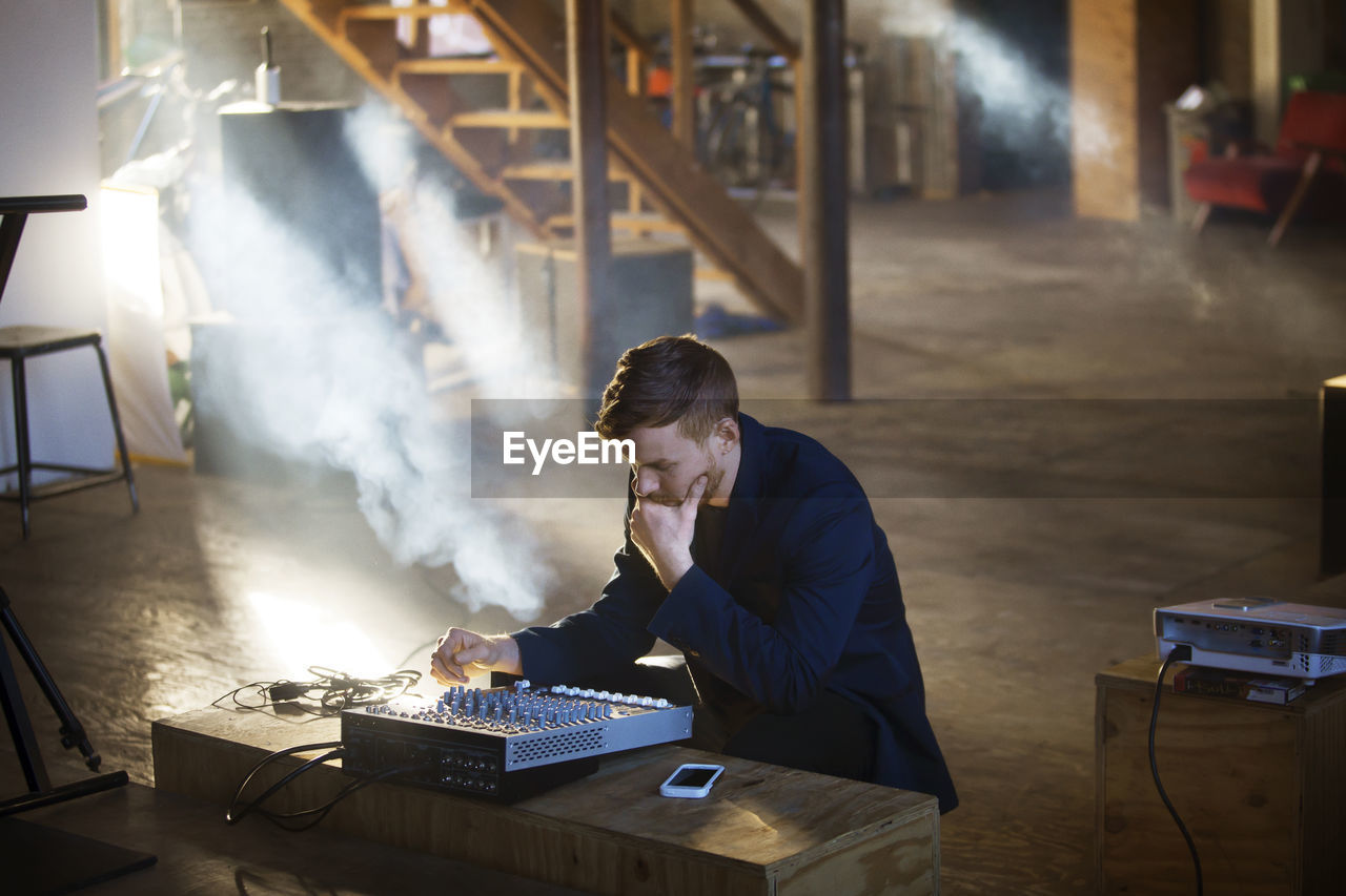 one person, table, indoors, real people, business, technology, men, smoke - physical structure, waist up, occupation, sitting, business person, working, desk, young adult, adult, computer, furniture, males, electric lamp