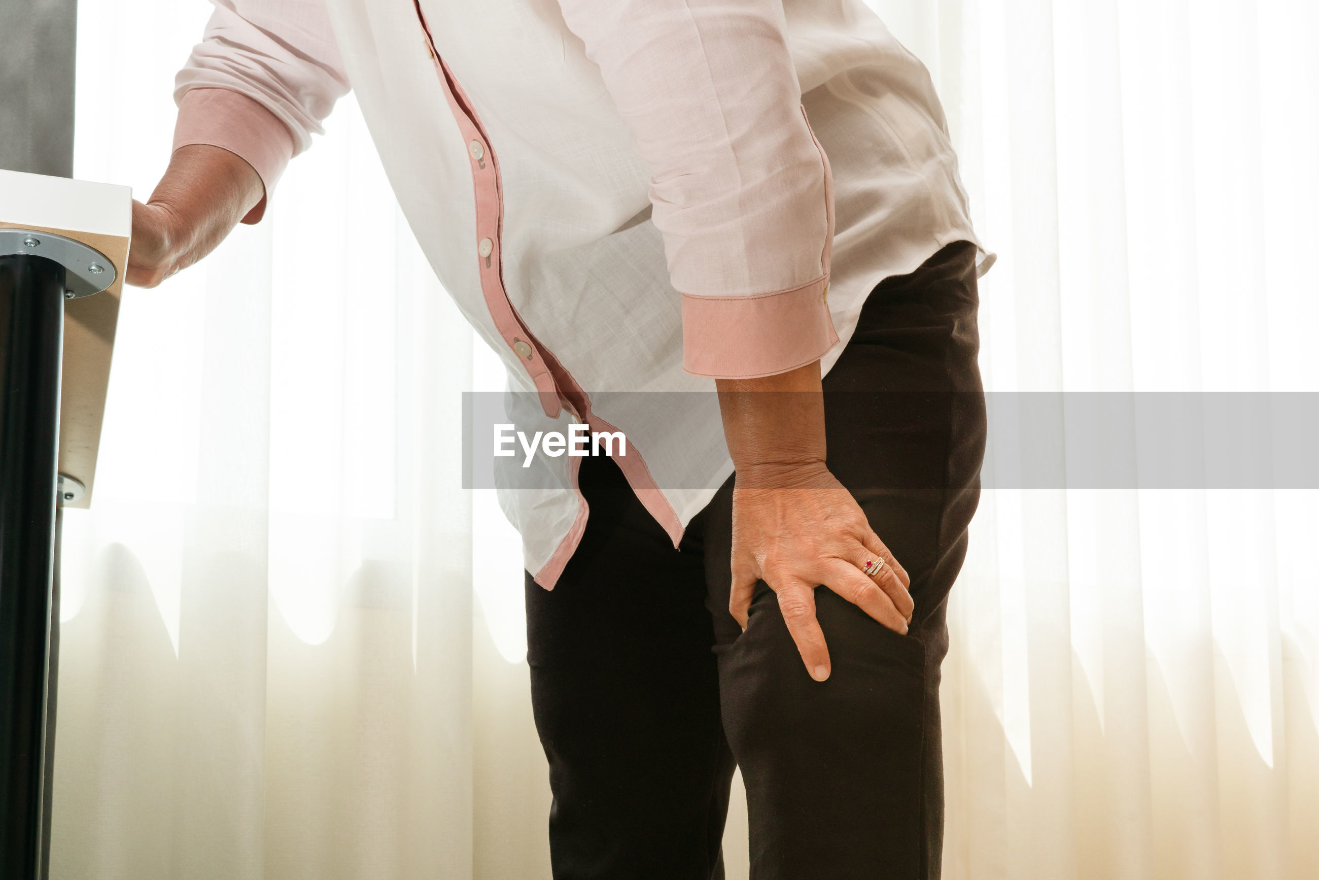 Midsection of woman with knee pain standing against curtain