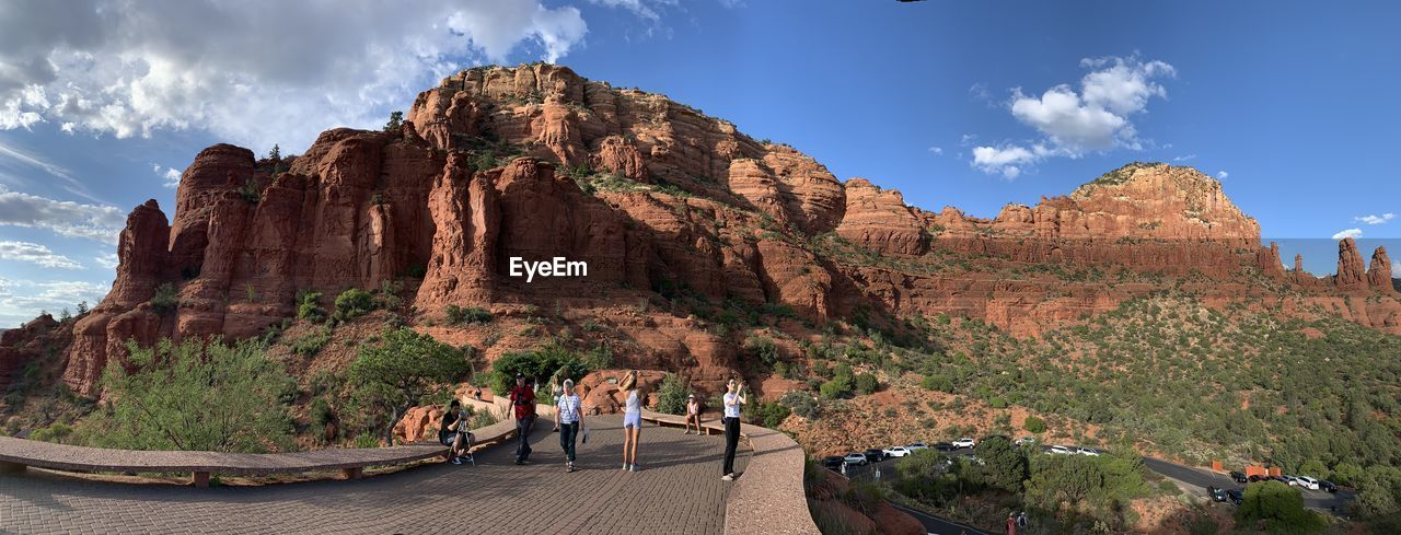PANORAMIC VIEW OF PEOPLE WALKING ON ROCK FORMATION
