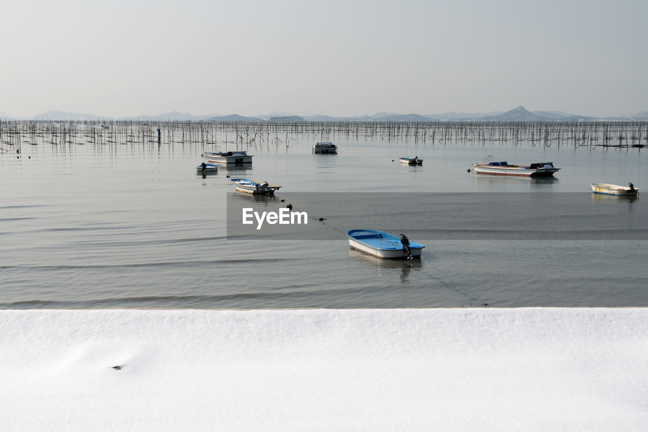 BOATS MOORED AT SEA AGAINST CLEAR SKY