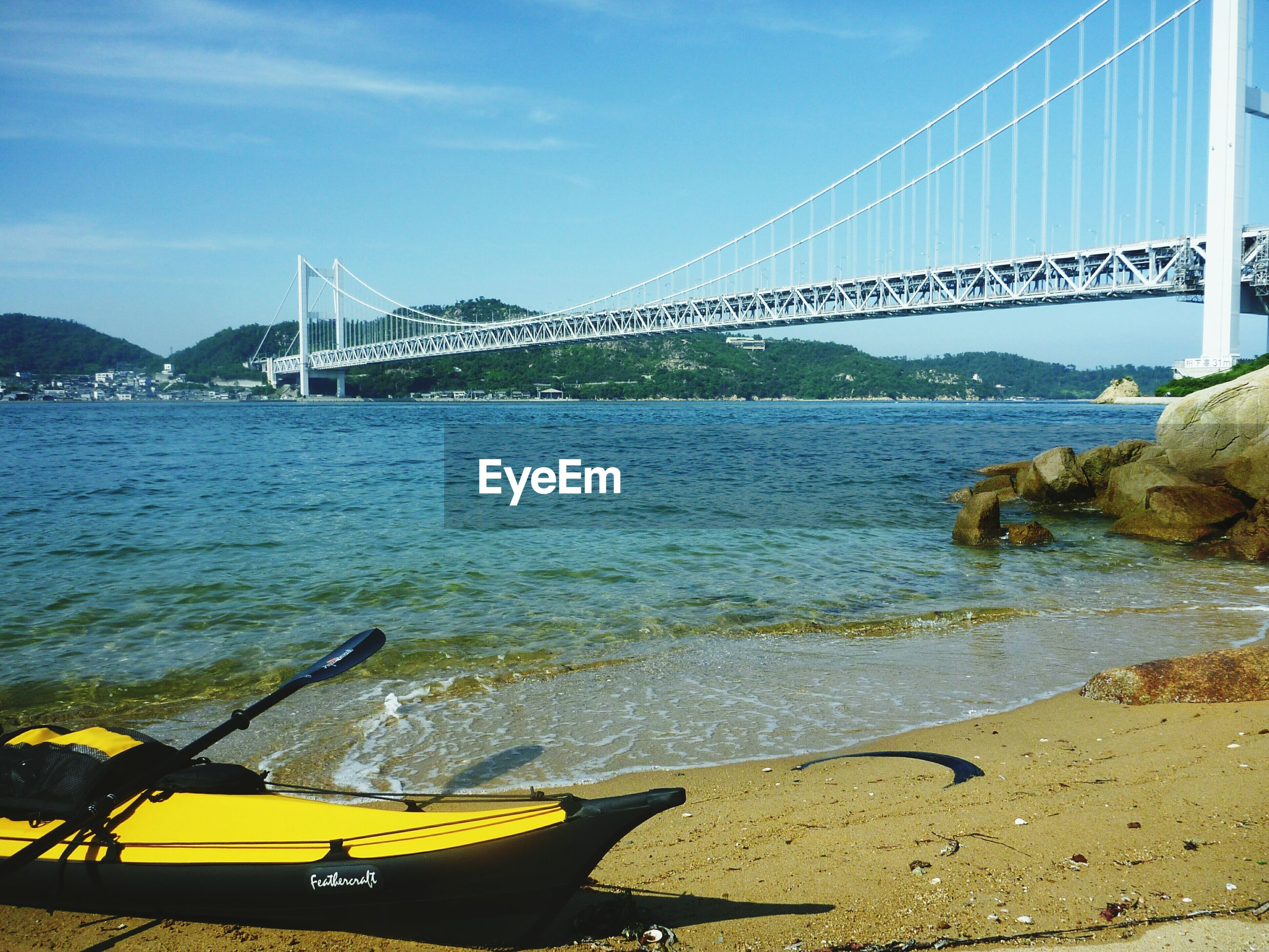 water, sea, transportation, sky, nautical vessel, beach, boat, tranquility, scenics, shore, blue, nature, bridge - man made structure, tranquil scene, mountain, beauty in nature, sunlight, mode of transport, river, connection