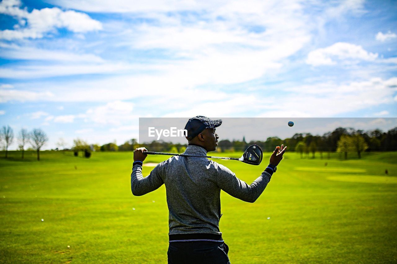 one person, leisure activity, green color, rear view, standing, sky, real people, grass, field, day, outdoors, lifestyles, sport, golf, men, sportsman, golf swing, beauty in nature, nature, golf course, golfer, adult, people