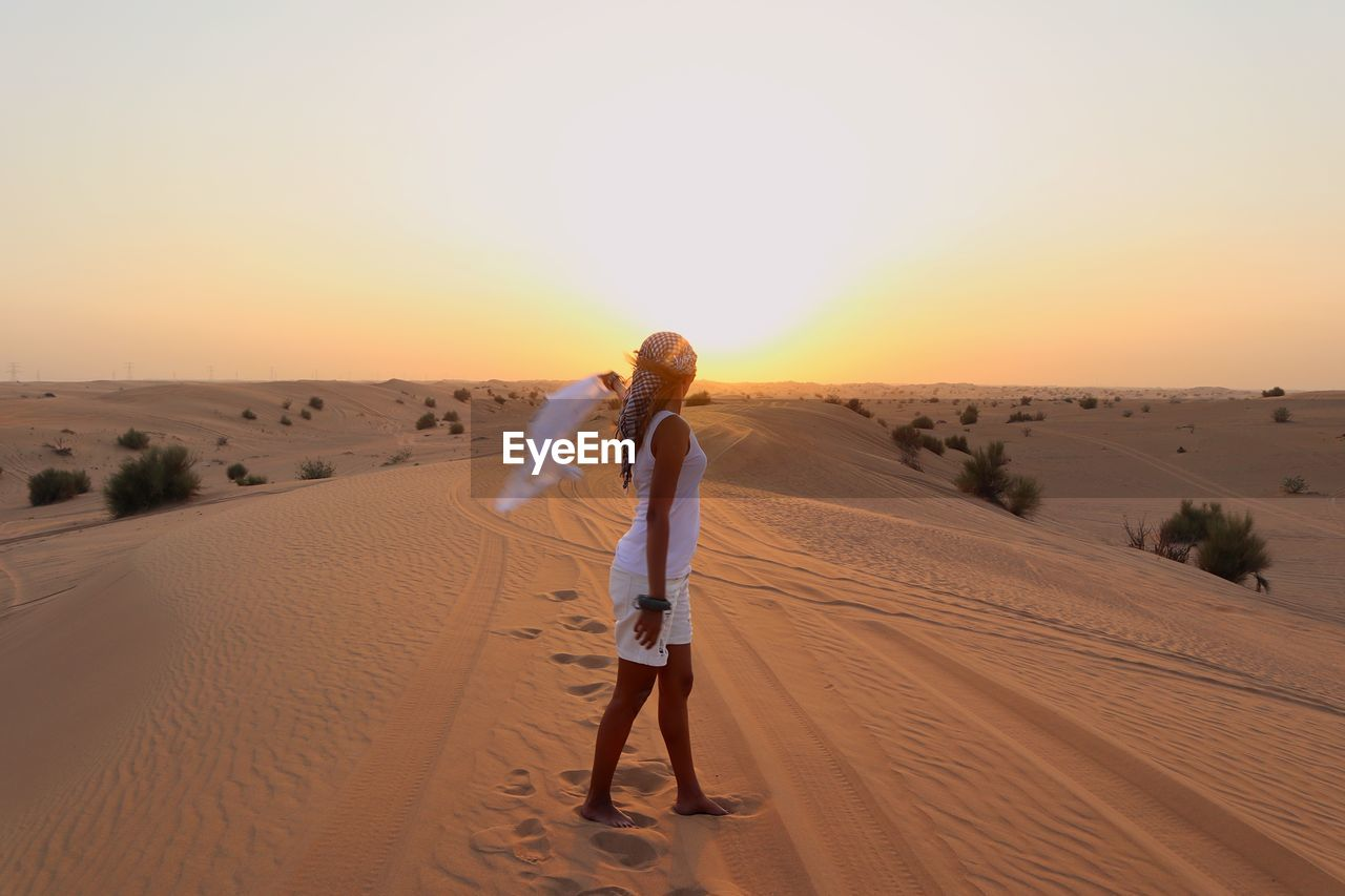 Side View Of Woman Standing On Sand At Desert Against Sky During Sunset
