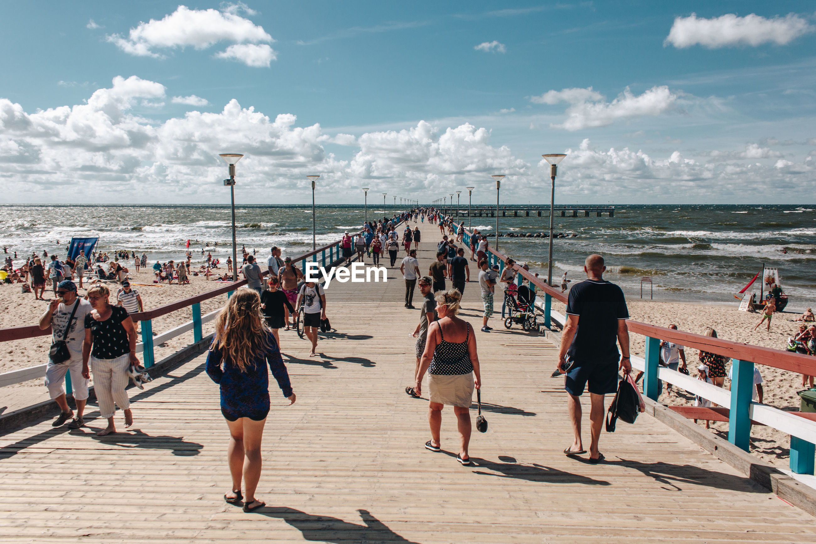 Group of people on boardwalk at beach against sky