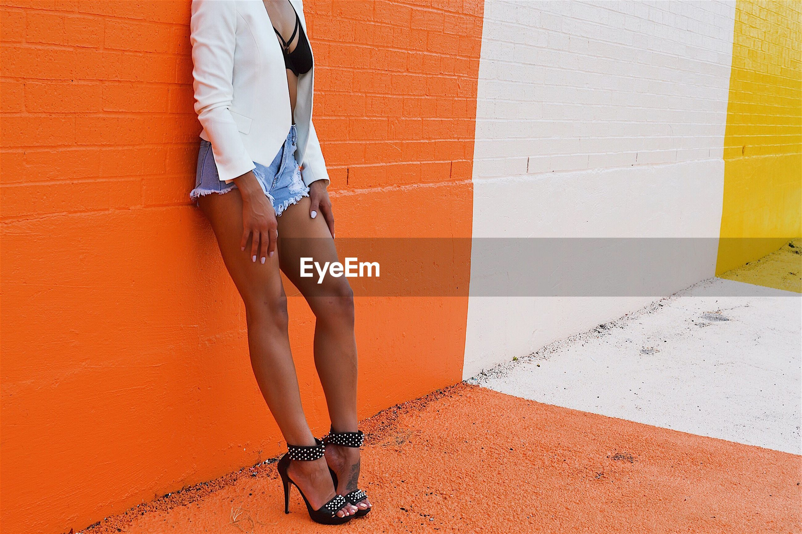 Low section of woman in hot pants leaning on orange wall