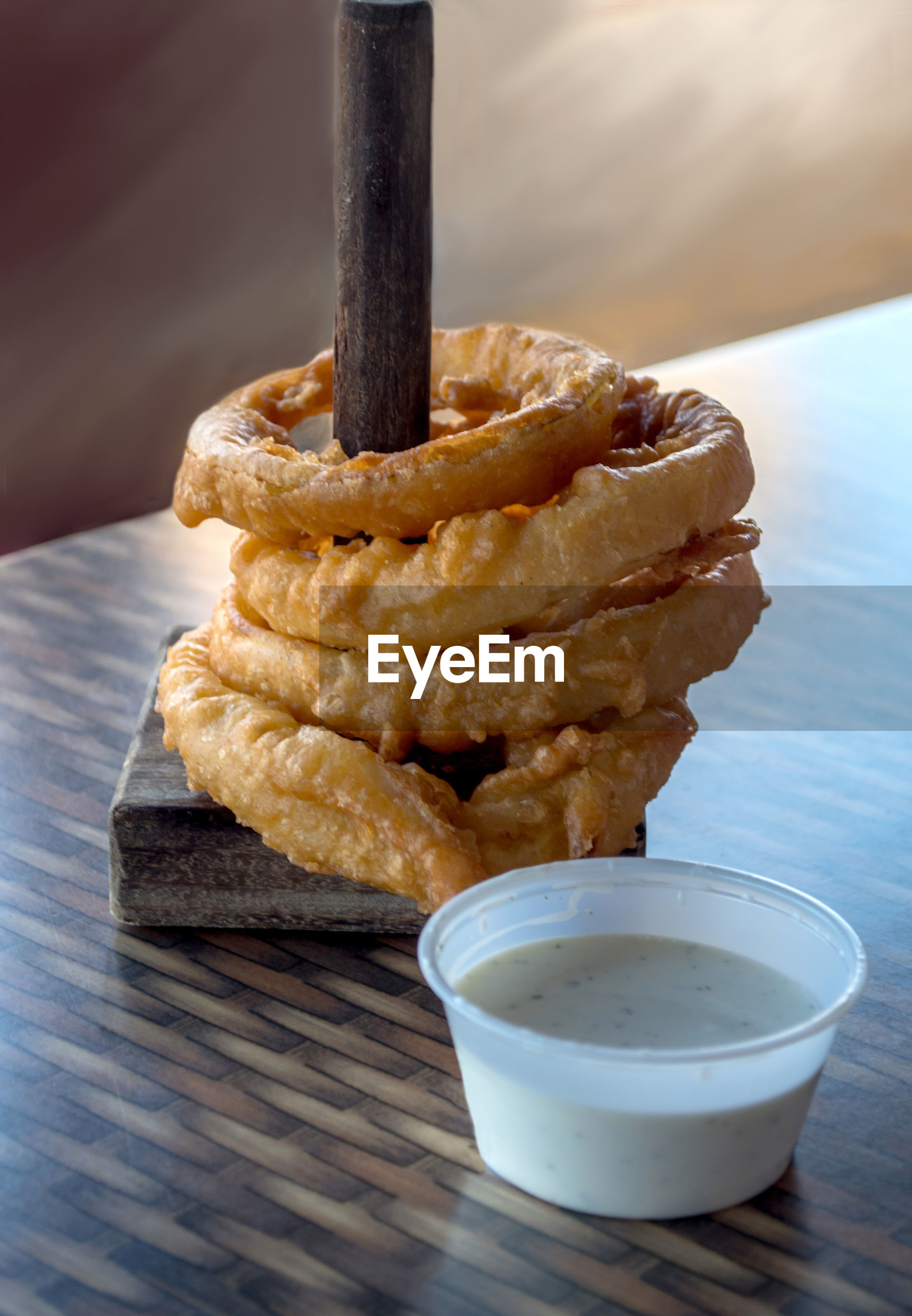 Stack of crispy, deep fried onion rings served on a spool with dipping sauce