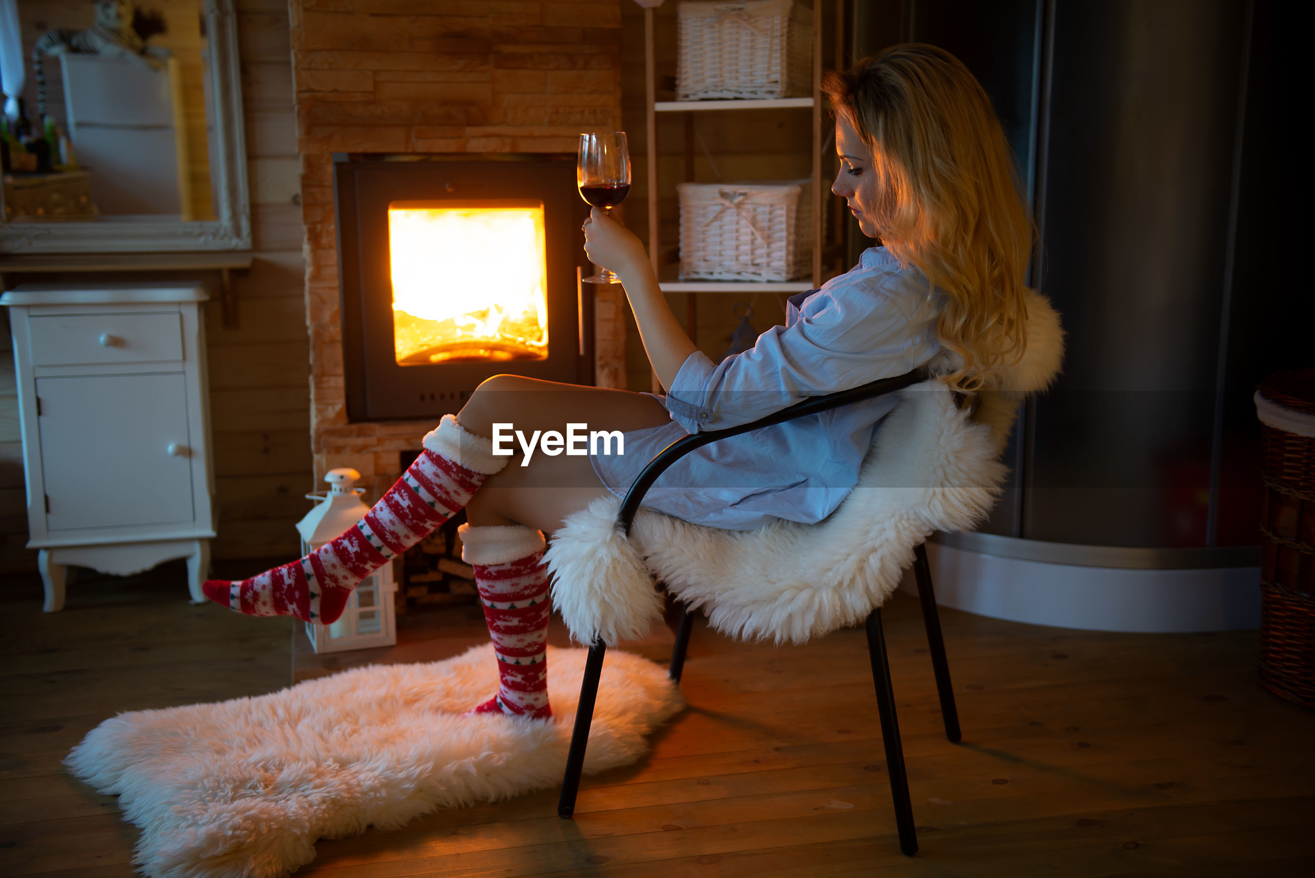 Woman with wine glass relaxing at the fireplace at home