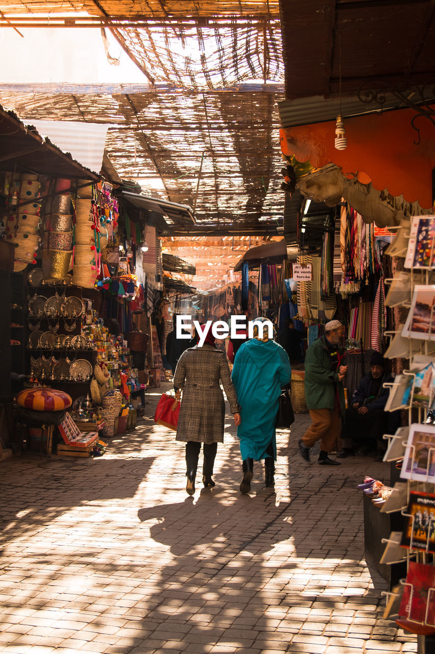 retail, real people, rear view, market, men, sunlight, walking, group of people, women, store, shopping, architecture, shadow, lifestyles, market stall, adult, for sale, people, full length, day, the way forward, sale, outdoors, retail display, street market, buying, consumerism
