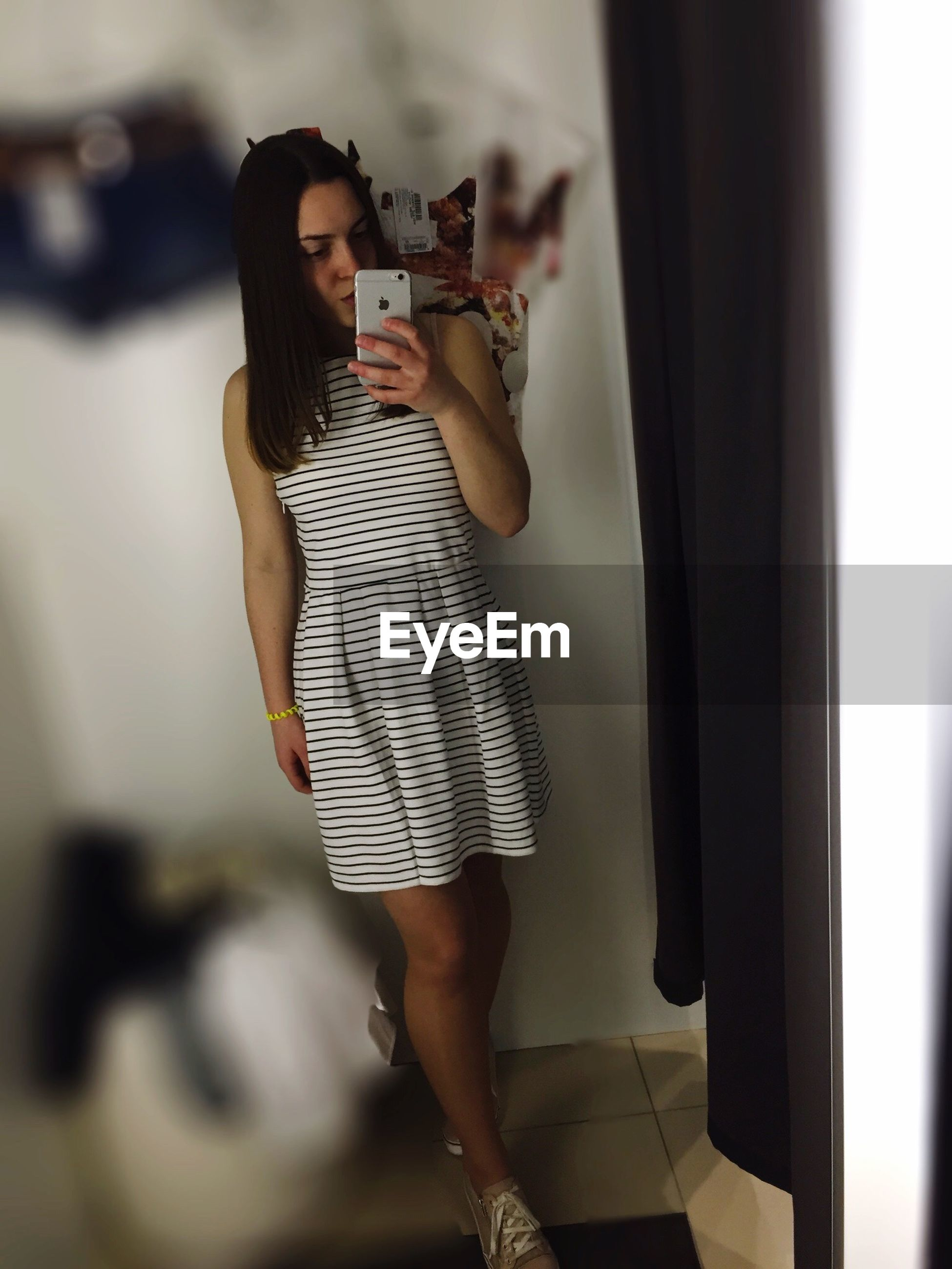 lifestyles, young adult, young women, casual clothing, leisure activity, standing, person, indoors, three quarter length, front view, holding, fashion, focus on foreground, long hair, sensuality, wireless technology
