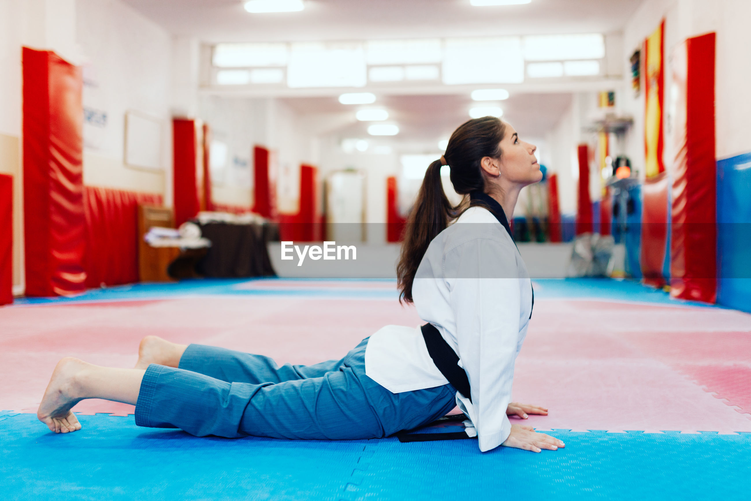 Side view full length of young woman exercising