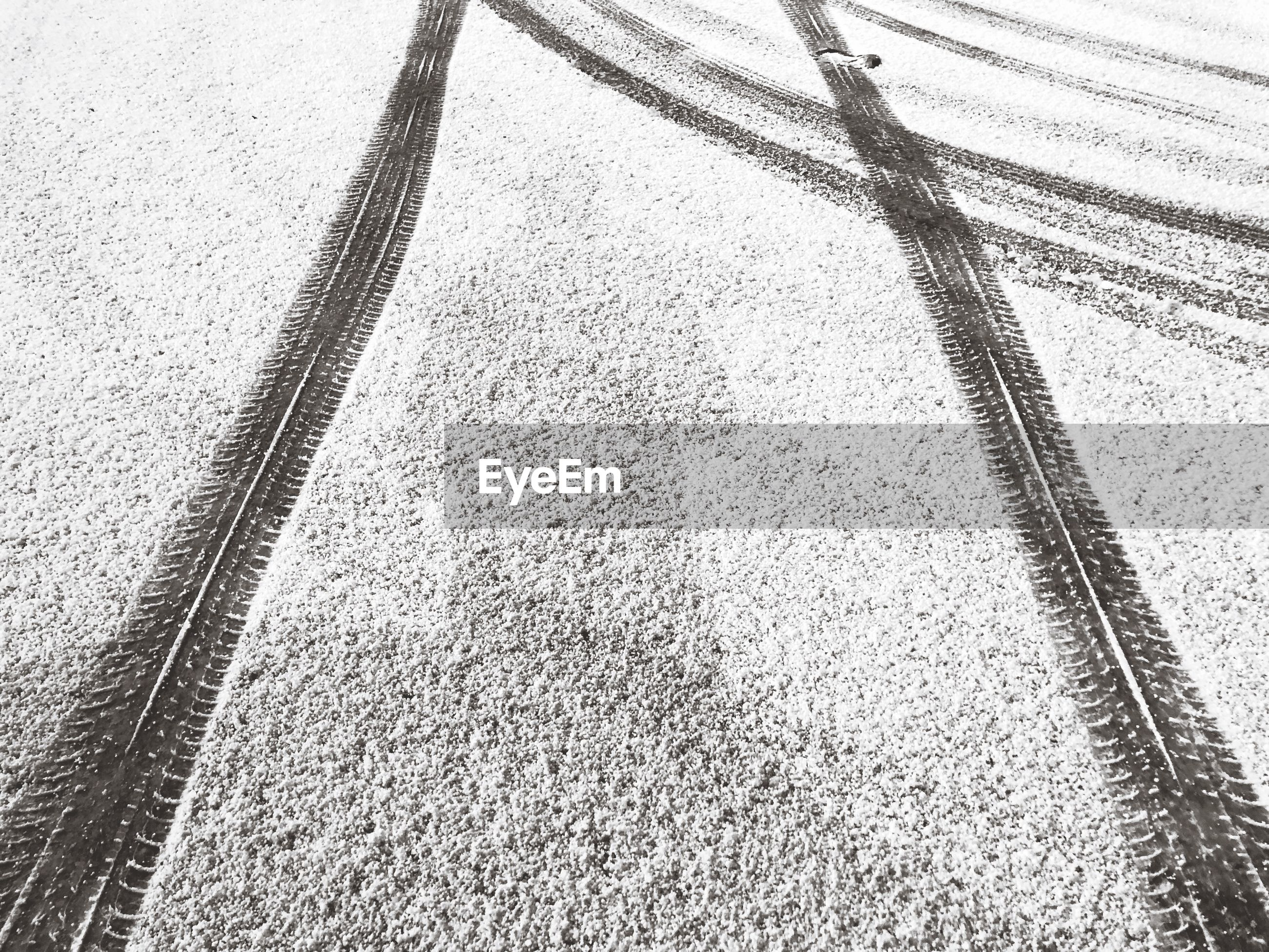 High angle view of tire tracks on snow covered land