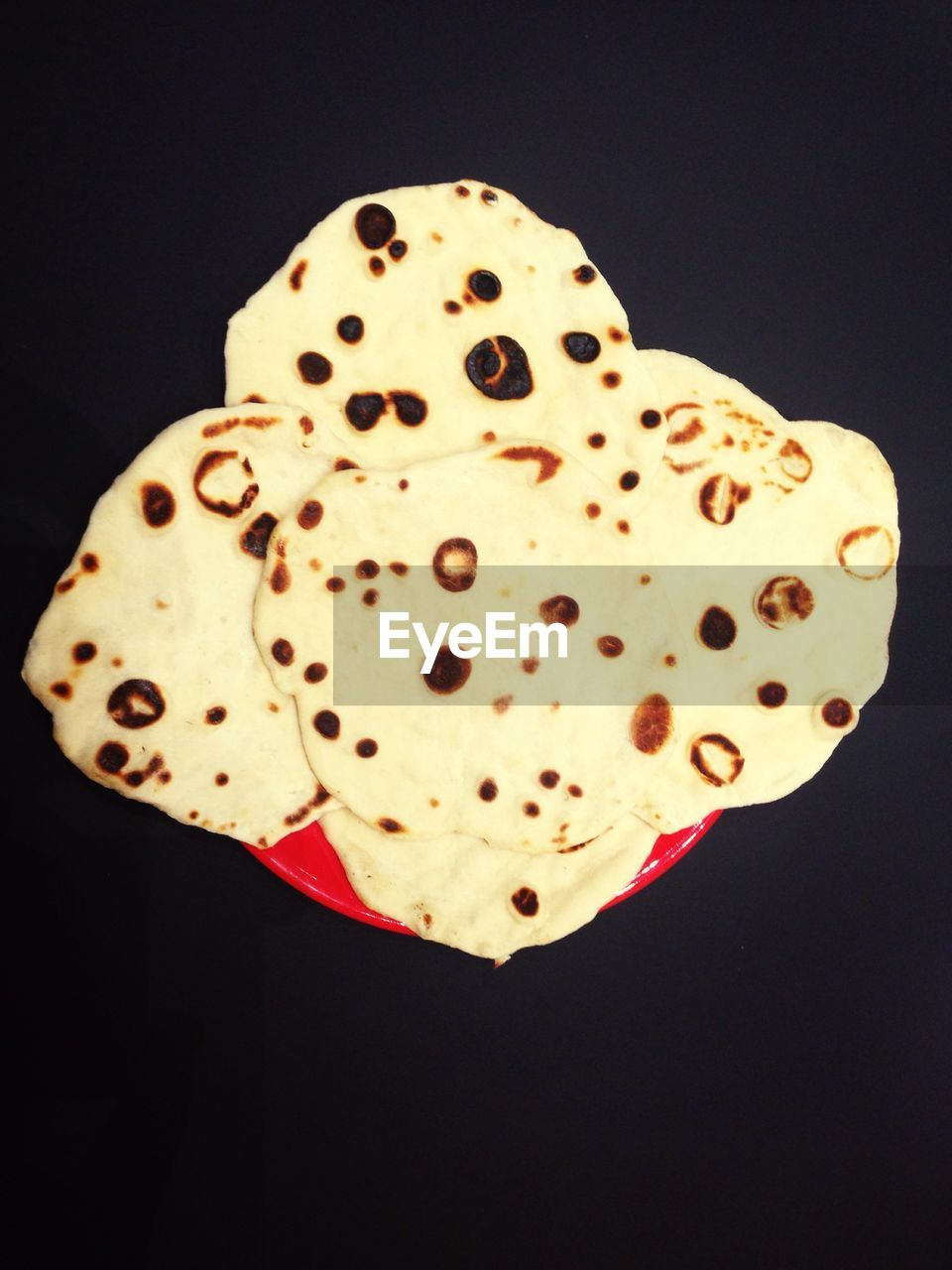 Close-up of naan breads in plate against black background