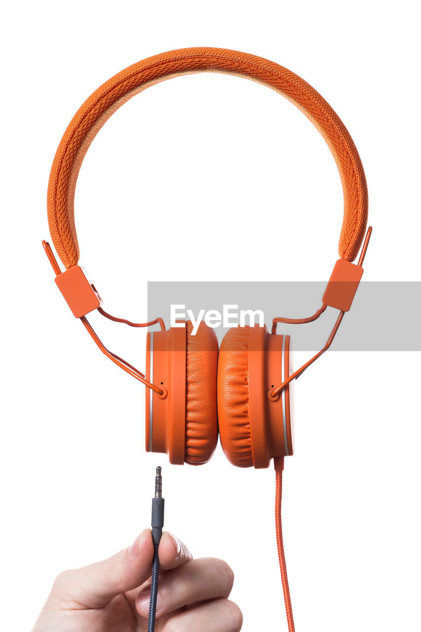 Cropped image of hand with headphones against white background