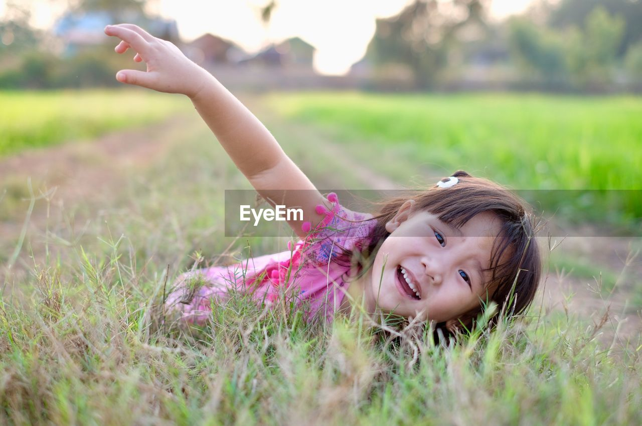 grass, childhood, one person, field, child, portrait, plant, land, looking at camera, real people, smiling, leisure activity, women, casual clothing, girls, nature, happiness, emotion, lifestyles, females, cute, innocence, outdoors, human arm, arms raised