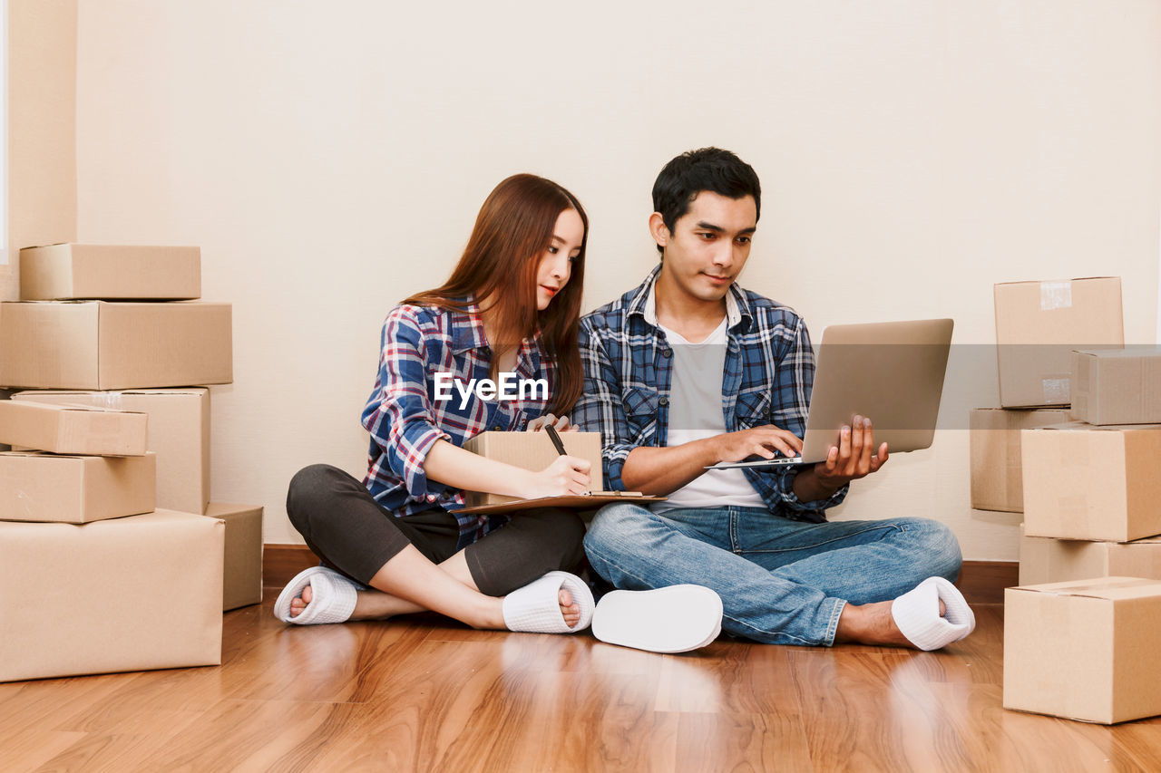Couple Working While Sitting On Floor At New Home