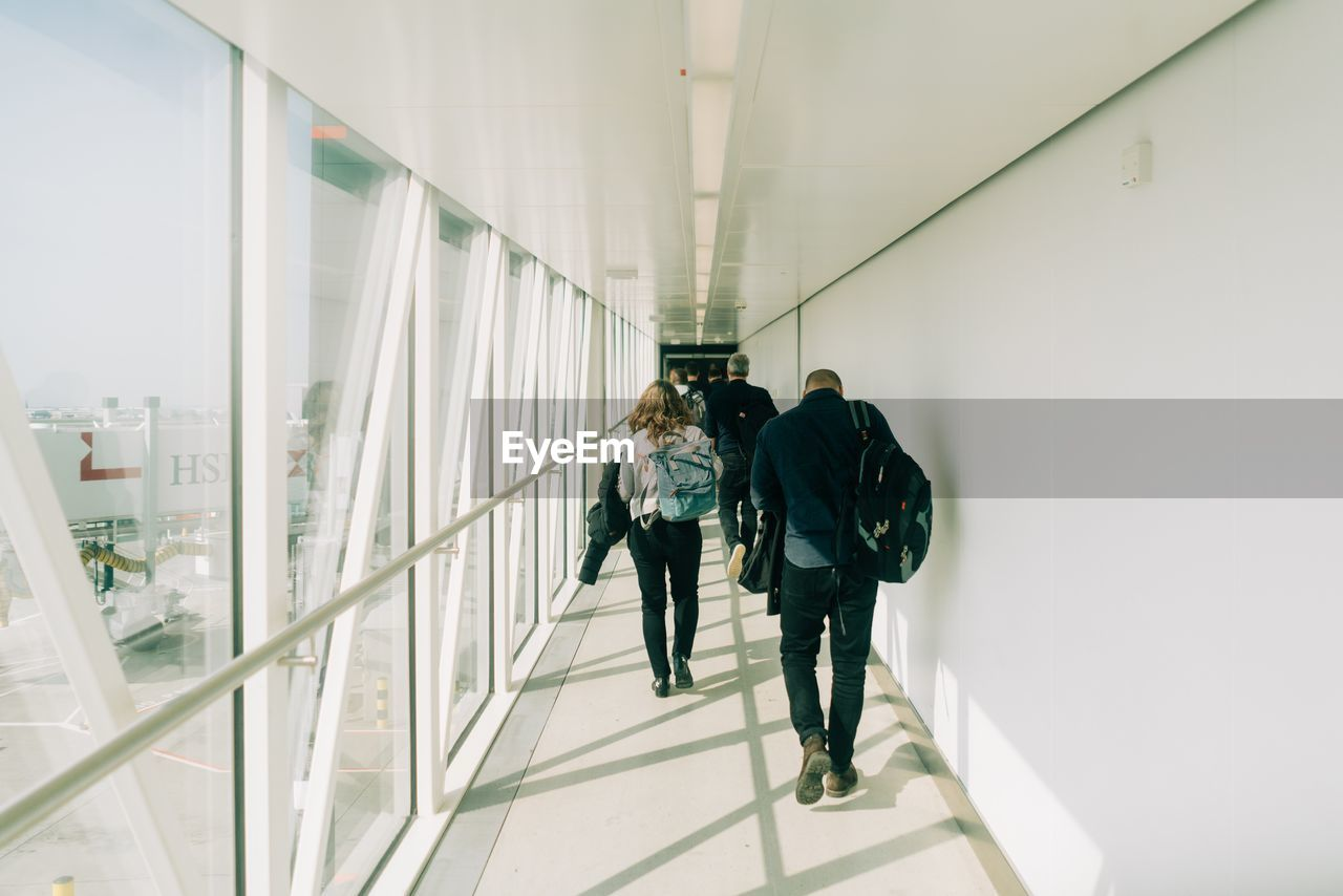 real people, architecture, walking, full length, men, indoors, rear view, built structure, group of people, lifestyles, people, casual clothing, adult, leisure activity, women, day, togetherness, modern, staircase, ceiling